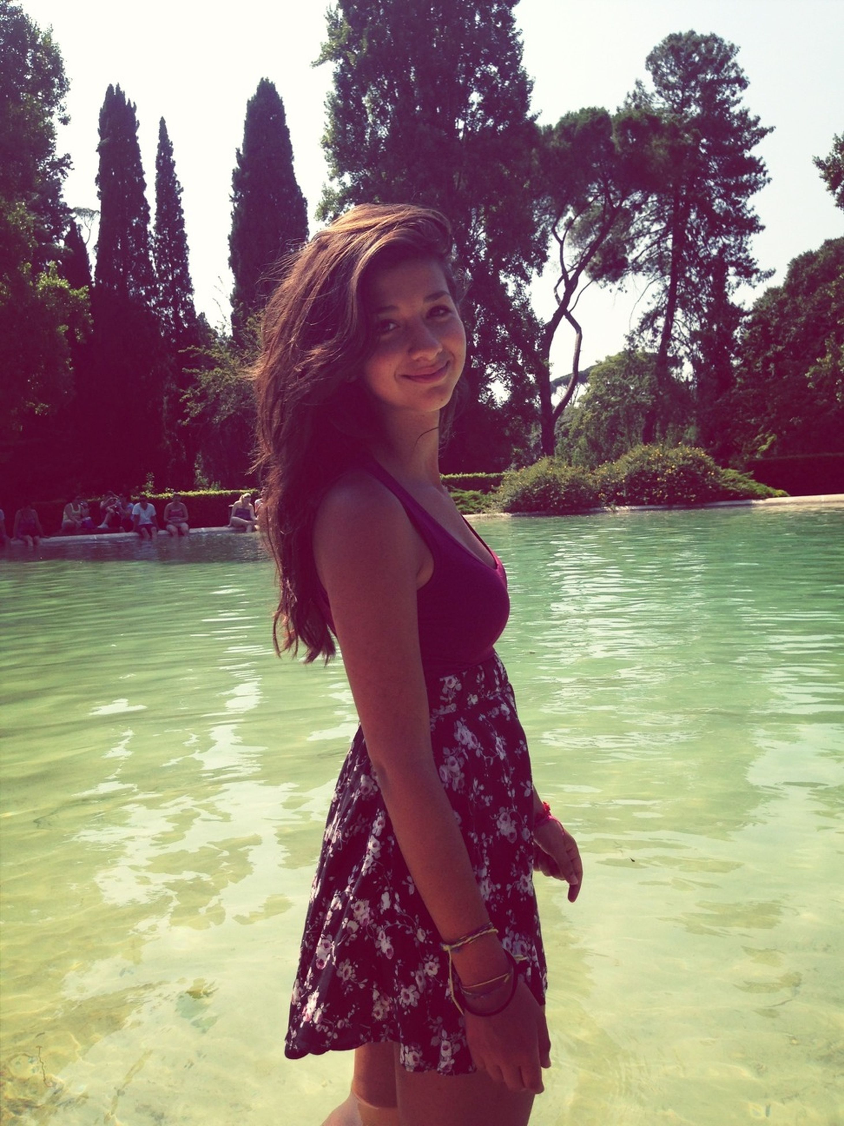 water, young adult, person, tree, lifestyles, young women, casual clothing, leisure activity, looking at camera, portrait, standing, front view, long hair, three quarter length, smiling, lake, river