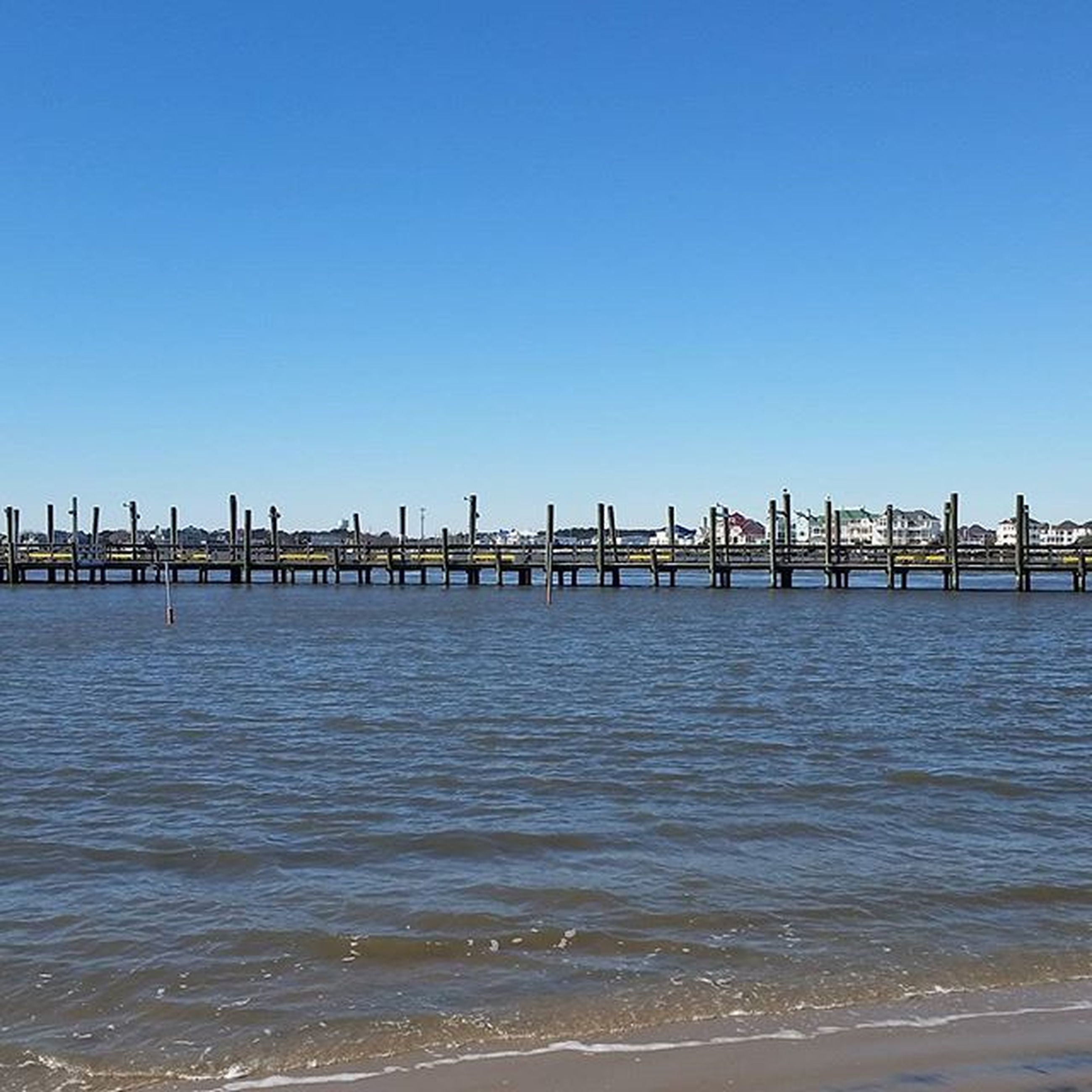 water, sea, clear sky, copy space, blue, pier, beach, tranquil scene, tranquility, built structure, nature, wooden post, scenics, beauty in nature, waterfront, wood - material, architecture, sky, shore, horizon over water