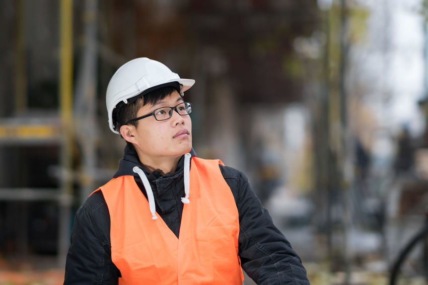 Young Asian engineer wearing protective work wear working on construction site. Outdoors Architecture Asian  Construction Site Growth Improvement Man Plant Safety Hard Hat Work Asian Man Development Engineer Engineering Future Outdoors Person Protective Workwear Real Estate Safety Helmet Safety Jacket
