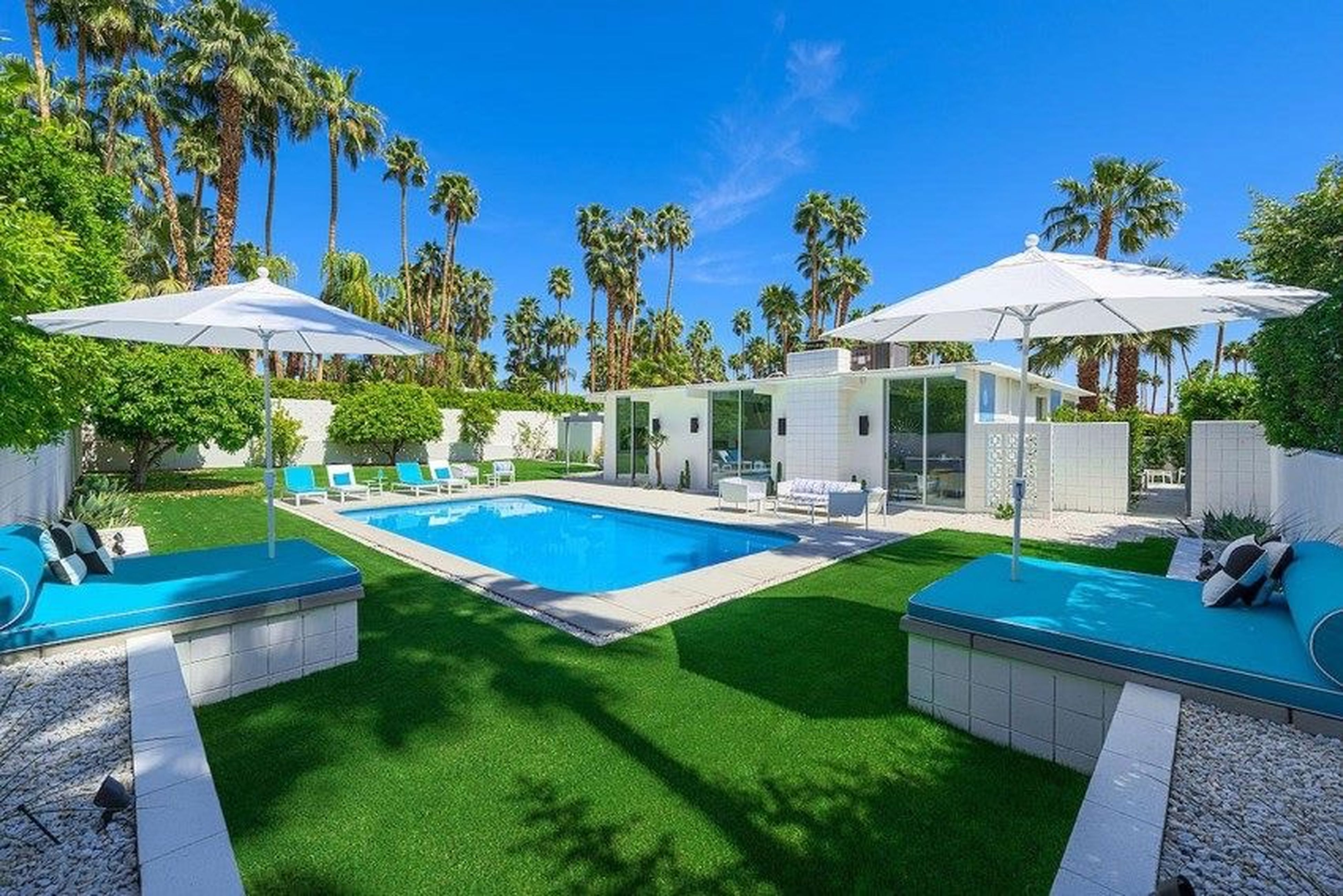 tree, swimming pool, blue, building exterior, built structure, architecture, palm tree, sunlight, sky, green color, tourist resort, water, shadow, grass, chair, day, house, lawn, growth, outdoors