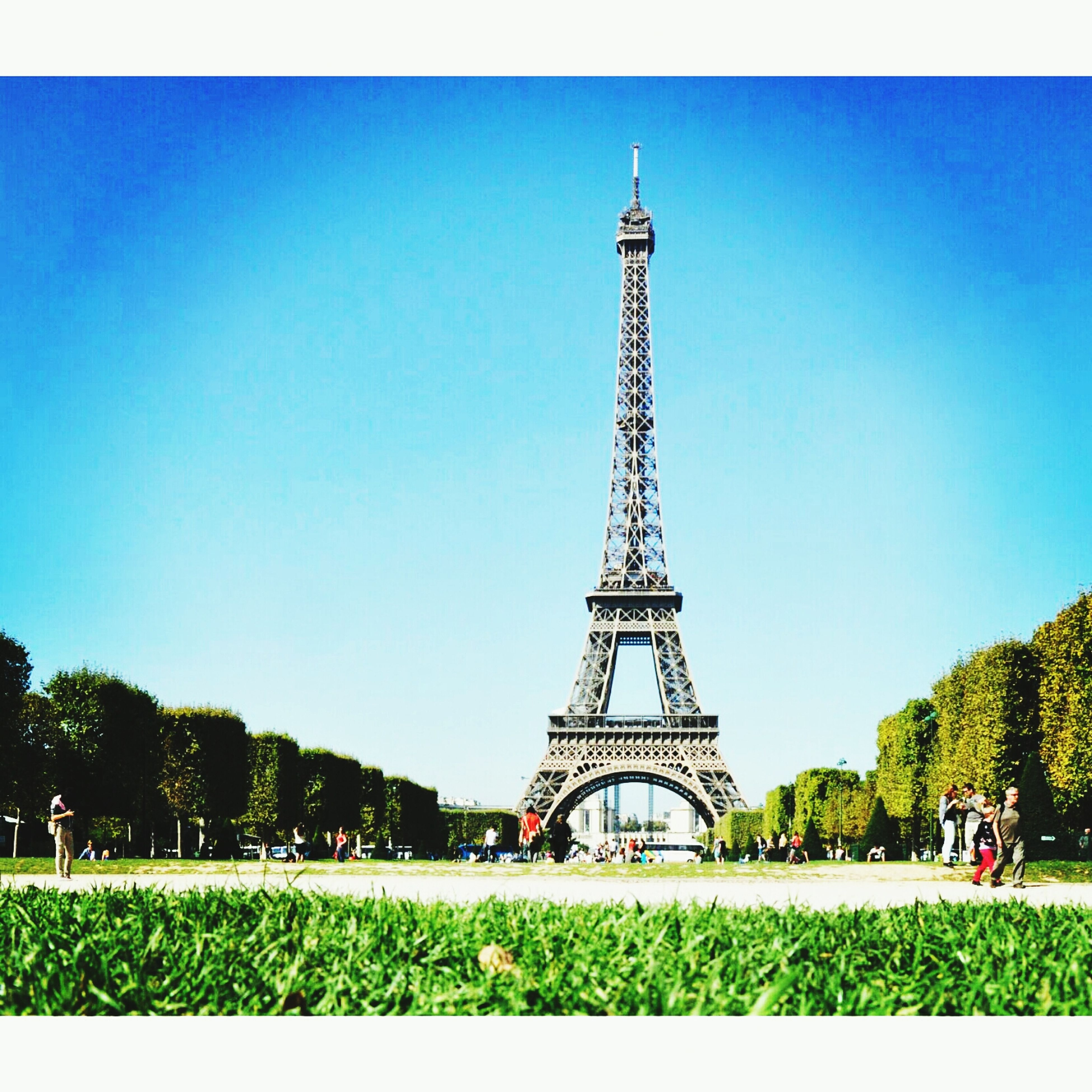 clear sky, built structure, architecture, tower, famous place, tree, eiffel tower, copy space, blue, tourism, travel destinations, grass, transfer print, international landmark, tall - high, building exterior, travel, capital cities, incidental people, metal