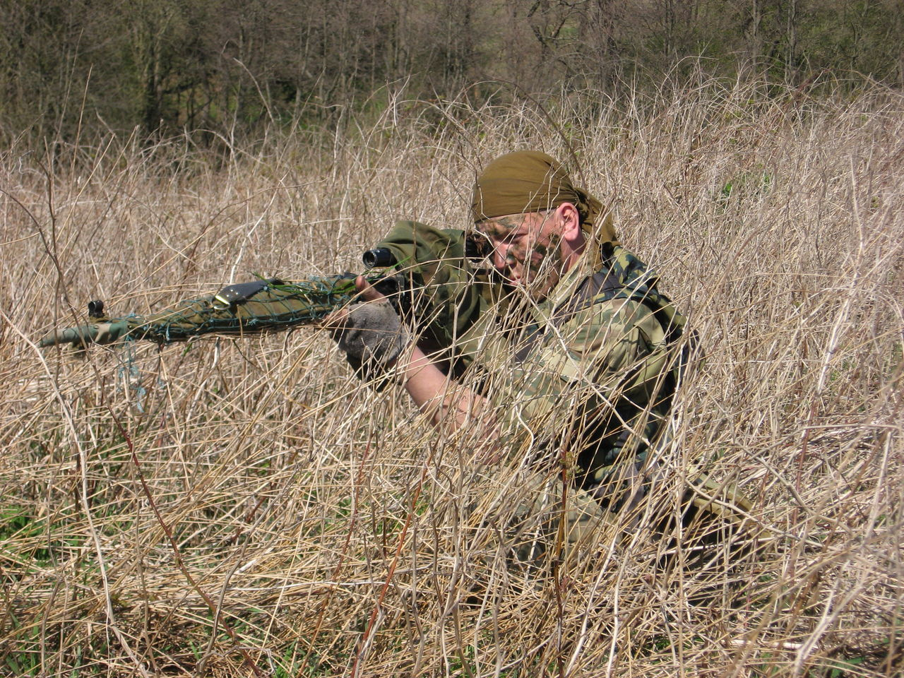 The sniper hides in the grass and aims at the target. Fighter of special troops. Trainings on carrying out firing practice and ambushes. Armed Forces Army Army Soldier Camouflage Camouflage Clothing Conflicts Gun Investigation Masking Men Military Military Uniform Rifle Saboteur Scout Sniper Soldier Special Troops Suit Syria  Ukraine Uniform War Weapon