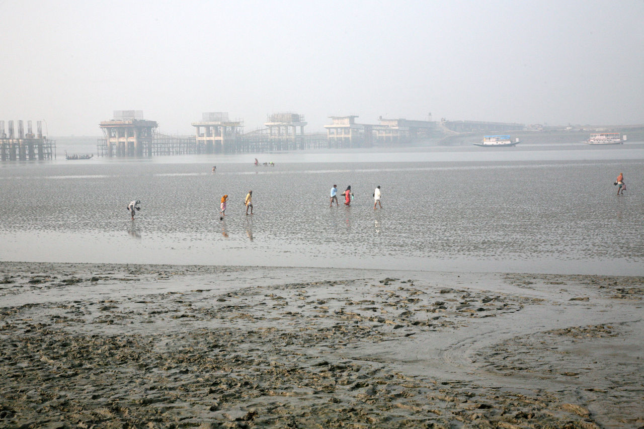 During low tide the water in the river Malta falls so low that people walk to the other shore in Canning Town, India on January 17, 2009. Canning Canning Town Coast Ebb India Large Group Of People Low Low Tide Malta River Mud People Shore Tidal Tide Town Walk Water West Bengal