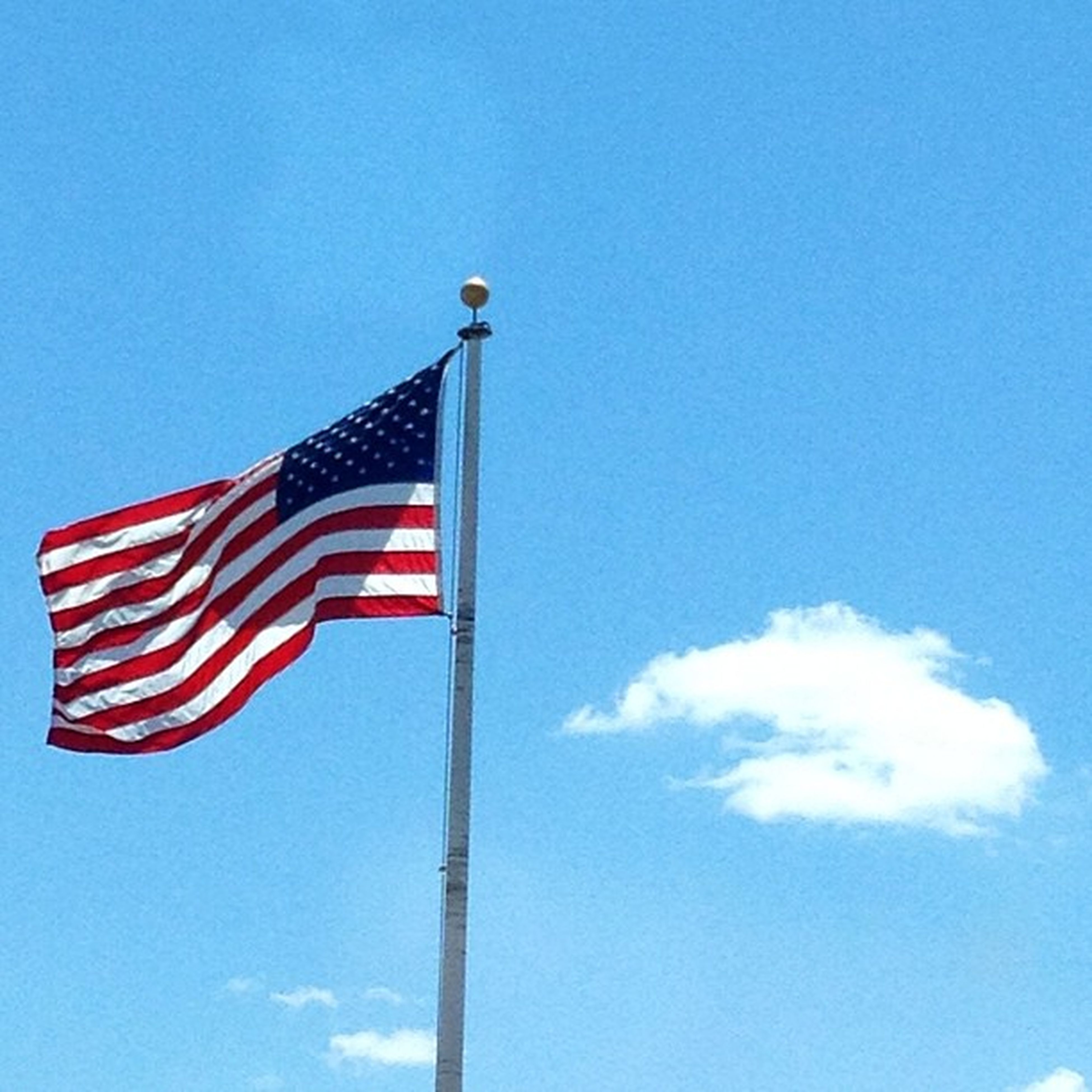 low angle view, patriotism, flag, identity, national flag, american flag, blue, clear sky, pole, striped, wind, sky, culture, flag pole, pride, red, day, copy space, fluttering, outdoors