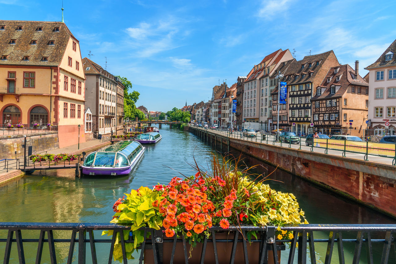 architecture, building exterior, built structure, water, canal, nautical vessel, transportation, mode of transport, sky, day, residential building, waterfront, outdoors, covered bridge, no people, bridge - man made structure, city, moored, flower, nature
