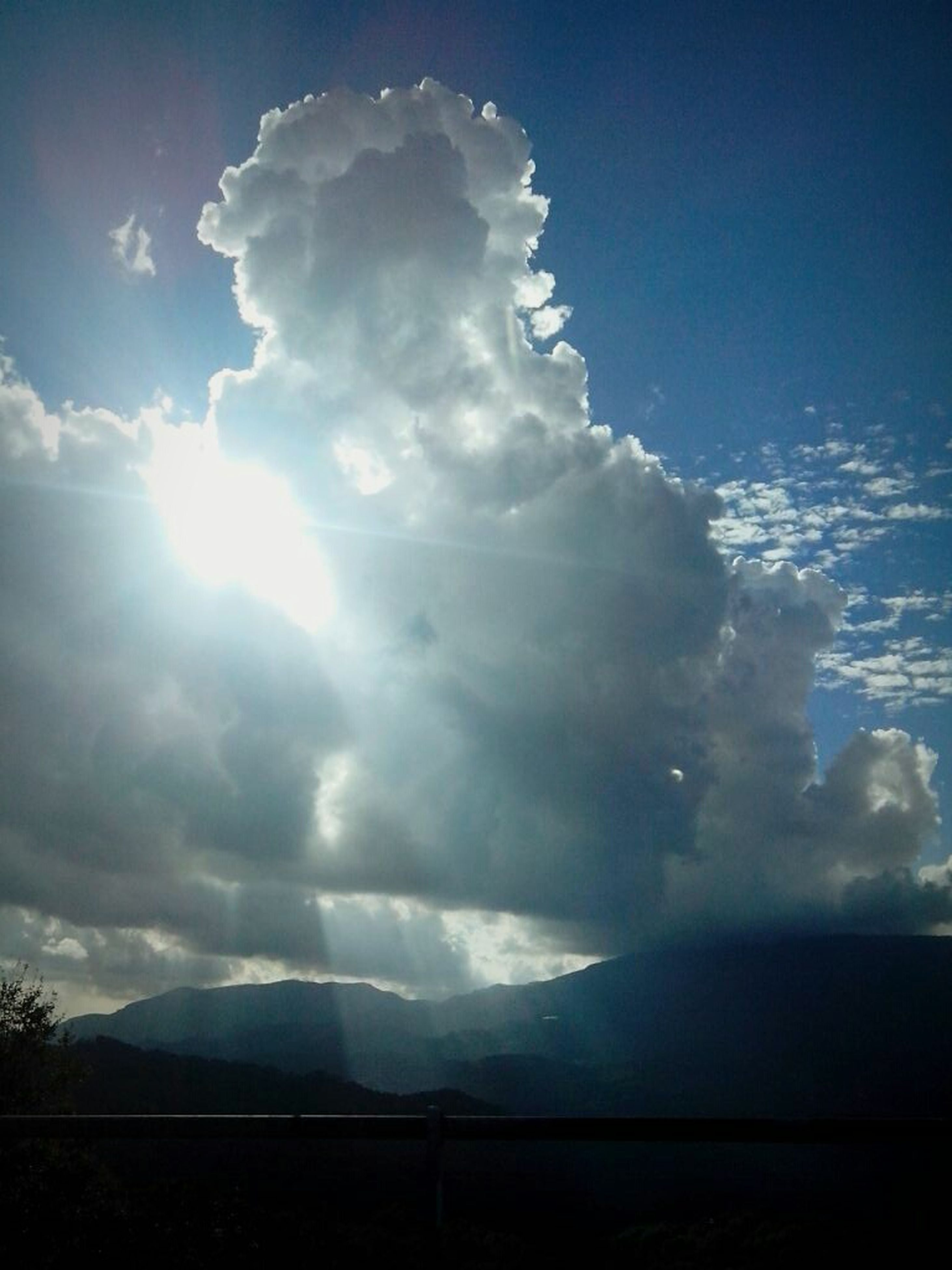 sky, tranquil scene, scenics, tranquility, beauty in nature, cloud - sky, sunbeam, nature, sun, mountain, landscape, cloud, silhouette, sunlight, idyllic, blue, cloudy, mountain range, non-urban scene, majestic