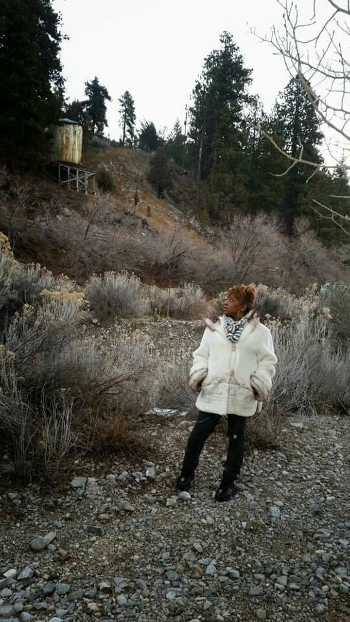 real people, one person, full length, tree, leisure activity, field, casual clothing, lifestyles, standing, plant, nature, young women, outdoors, day, young adult, warm clothing, sky, people
