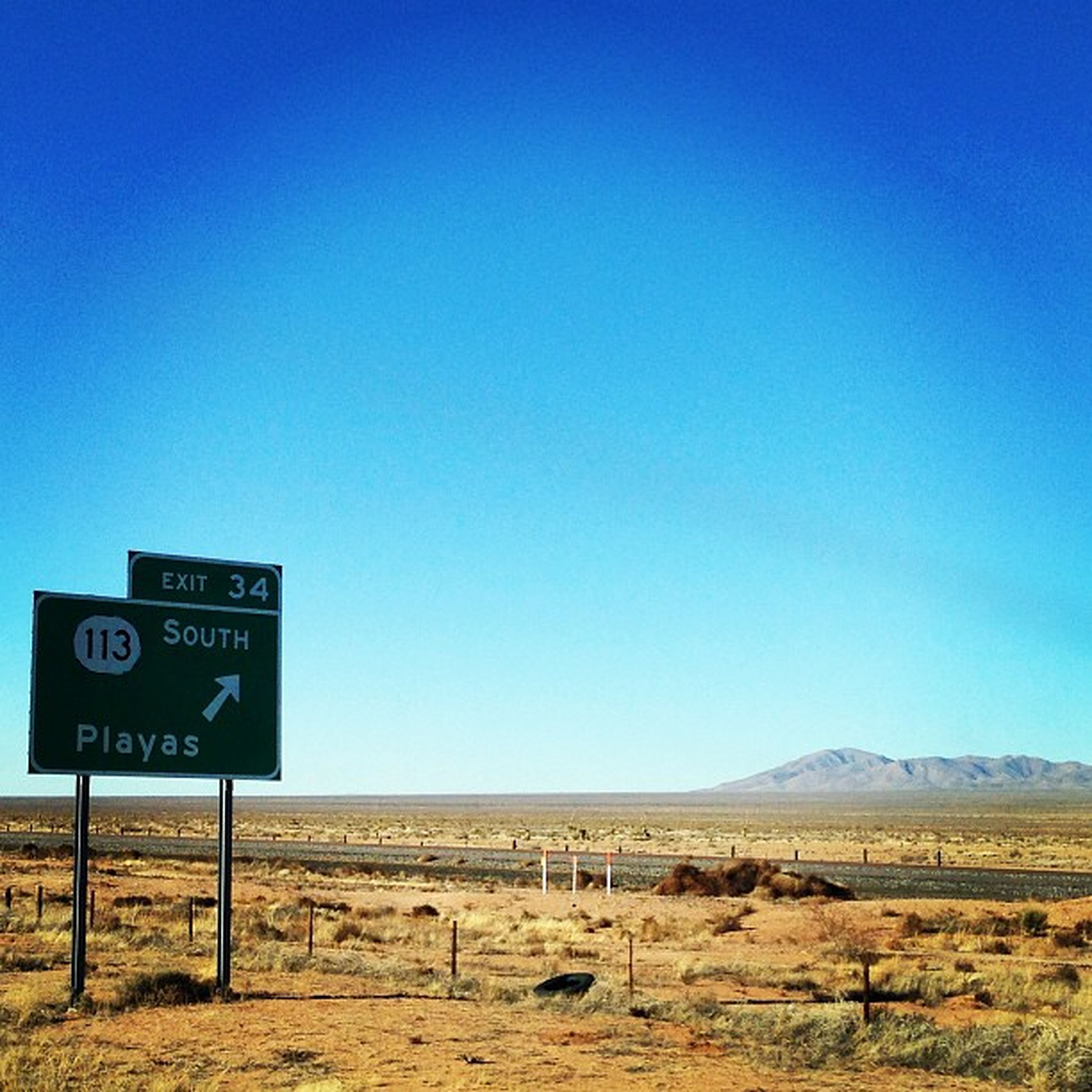 clear sky, copy space, blue, communication, landscape, western script, text, tranquil scene, tranquility, sign, guidance, nature, field, scenics, day, horizon over land, information sign, mountain, no people, non-urban scene