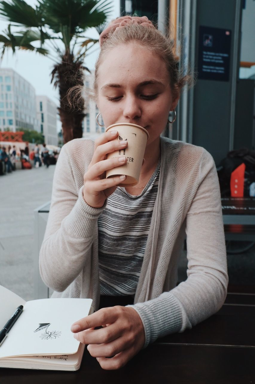 one person, real people, front view, young adult, coffee - drink, sitting, table, young women, casual clothing, drink, holding, university student, day, indoors, close-up, people