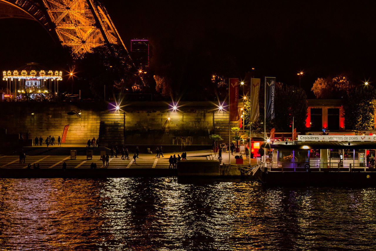 illuminated, night, water, waterfront, built structure, river, building exterior, architecture, reflection, nautical vessel, travel destinations, transportation, outdoors, large group of people, real people, city, sky