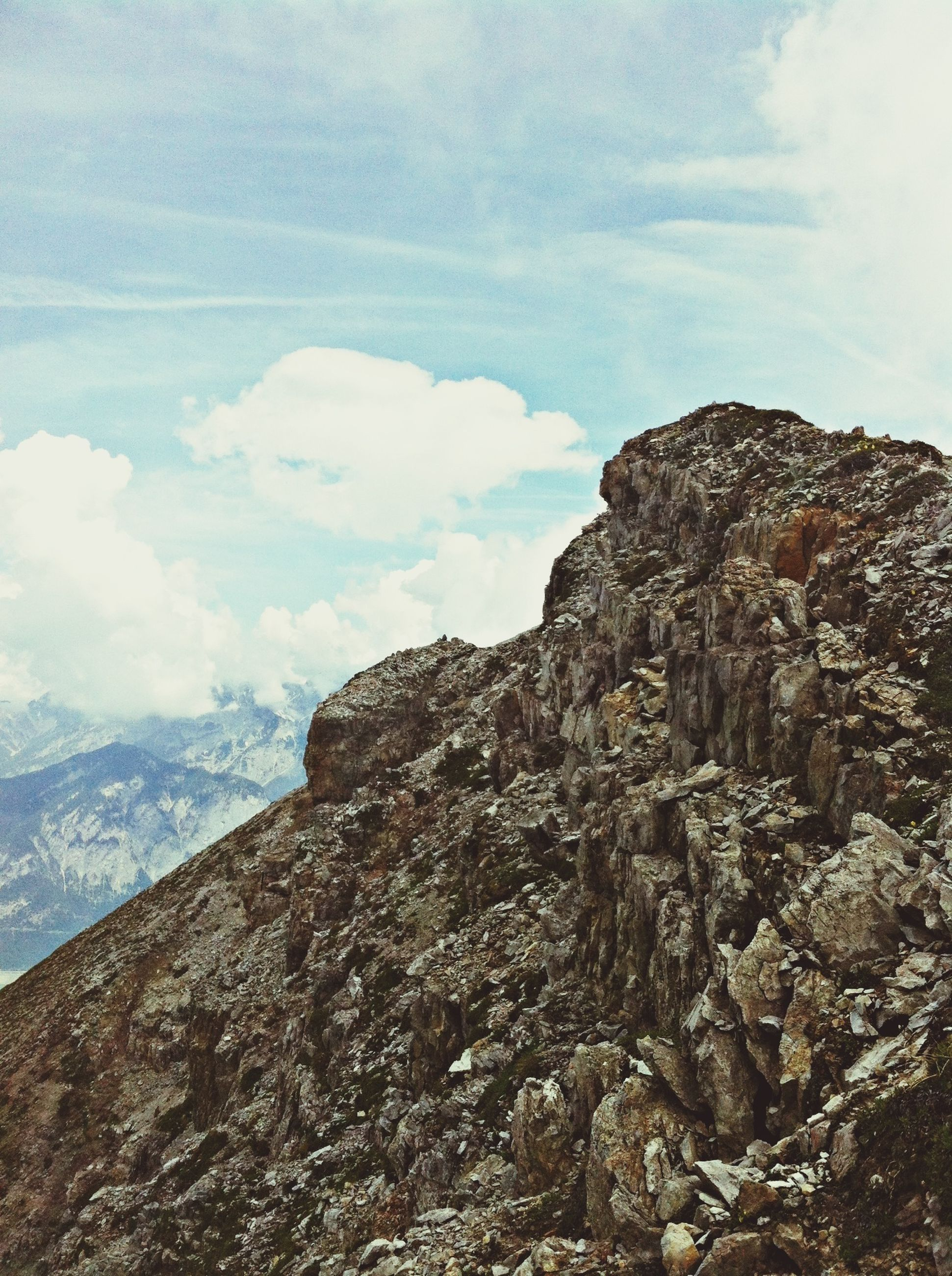 mountain, sky, low angle view, tranquility, rock formation, cloud - sky, tranquil scene, scenics, rocky mountains, rock - object, nature, beauty in nature, mountain range, cloud, geology, physical geography, landscape, day, non-urban scene, outdoors