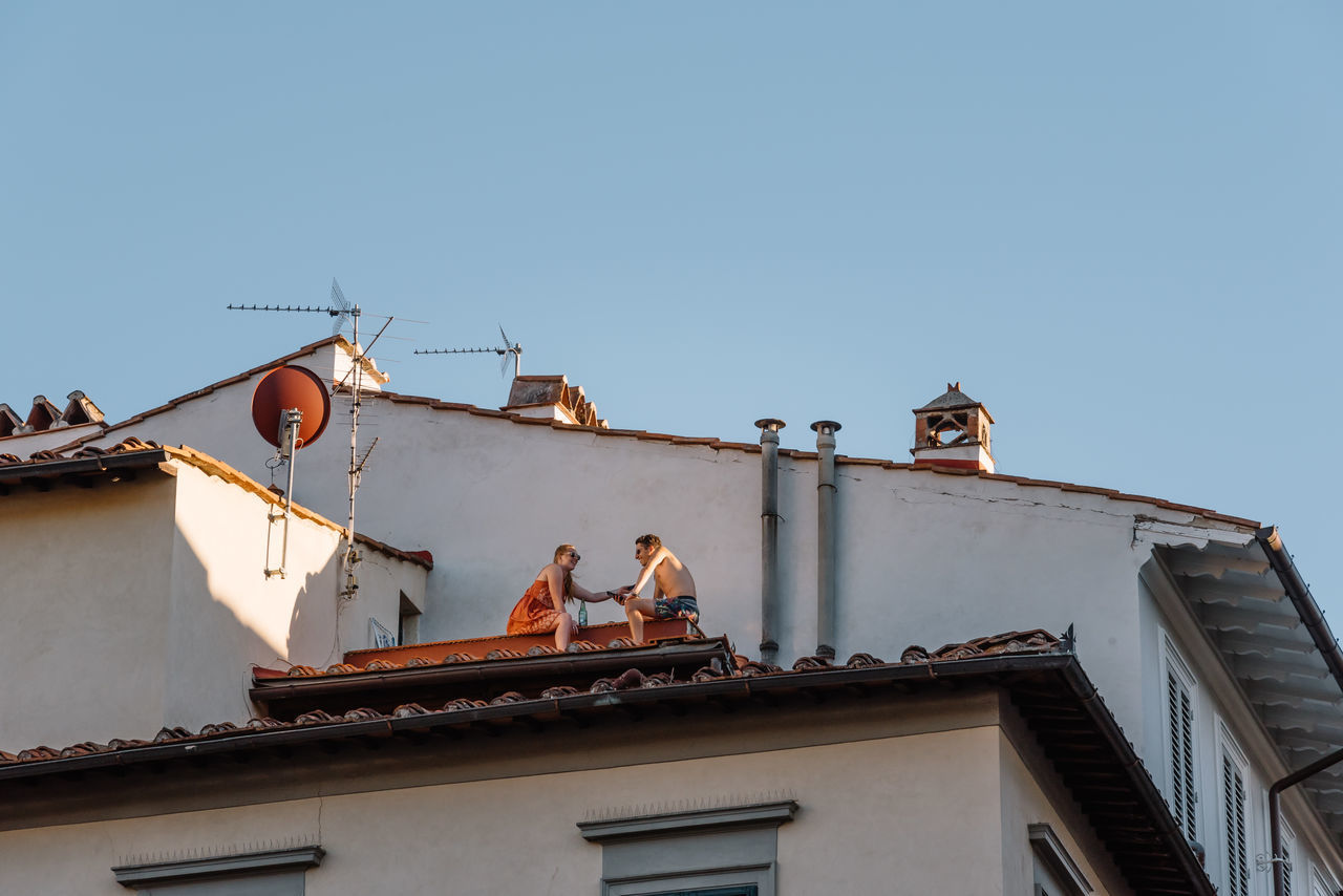 Couple sitting on a roof in historical city center of Florence Couple European Firenze Travel Tuscany antenna - aerial Architecture building exterior built structure Clear sky day destination europe famous place florence house italian landmark lifestyles Low angle view no people outdoors Roof roof tile sky telecommunications equipment television aerial tiled roof