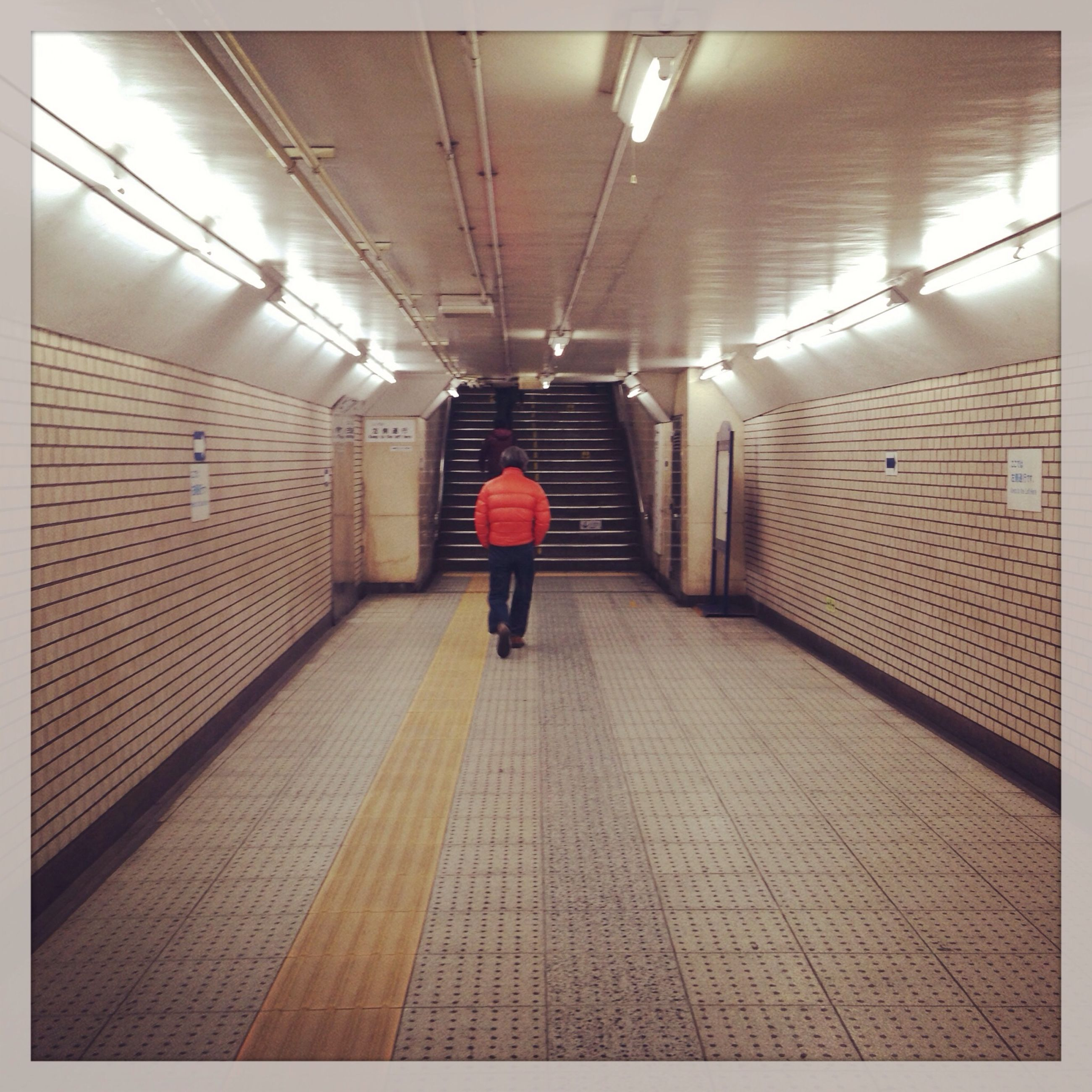 indoors, the way forward, corridor, full length, walking, rear view, architecture, illuminated, lifestyles, men, built structure, subway, tunnel, tiled floor, wall - building feature, flooring, ceiling, diminishing perspective