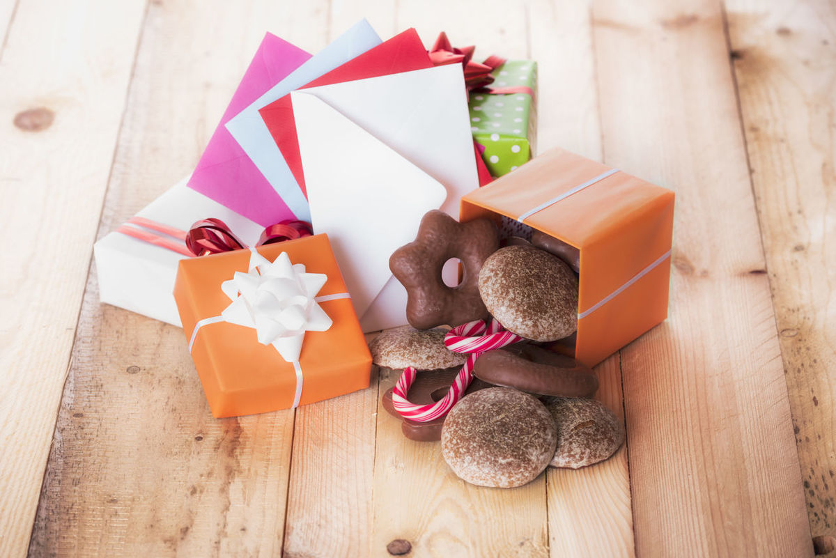 Gingerbread in a gift box near a stack of gifts and multicolored envelopes Opened Gifts Red Candies Wooden Table Birthday Presents Childhood Christmas Decoration Envelopes Family Time Gift Boxes Gingerbread Cookie Holiday Decor Holiday Gifts Xmas Sweets