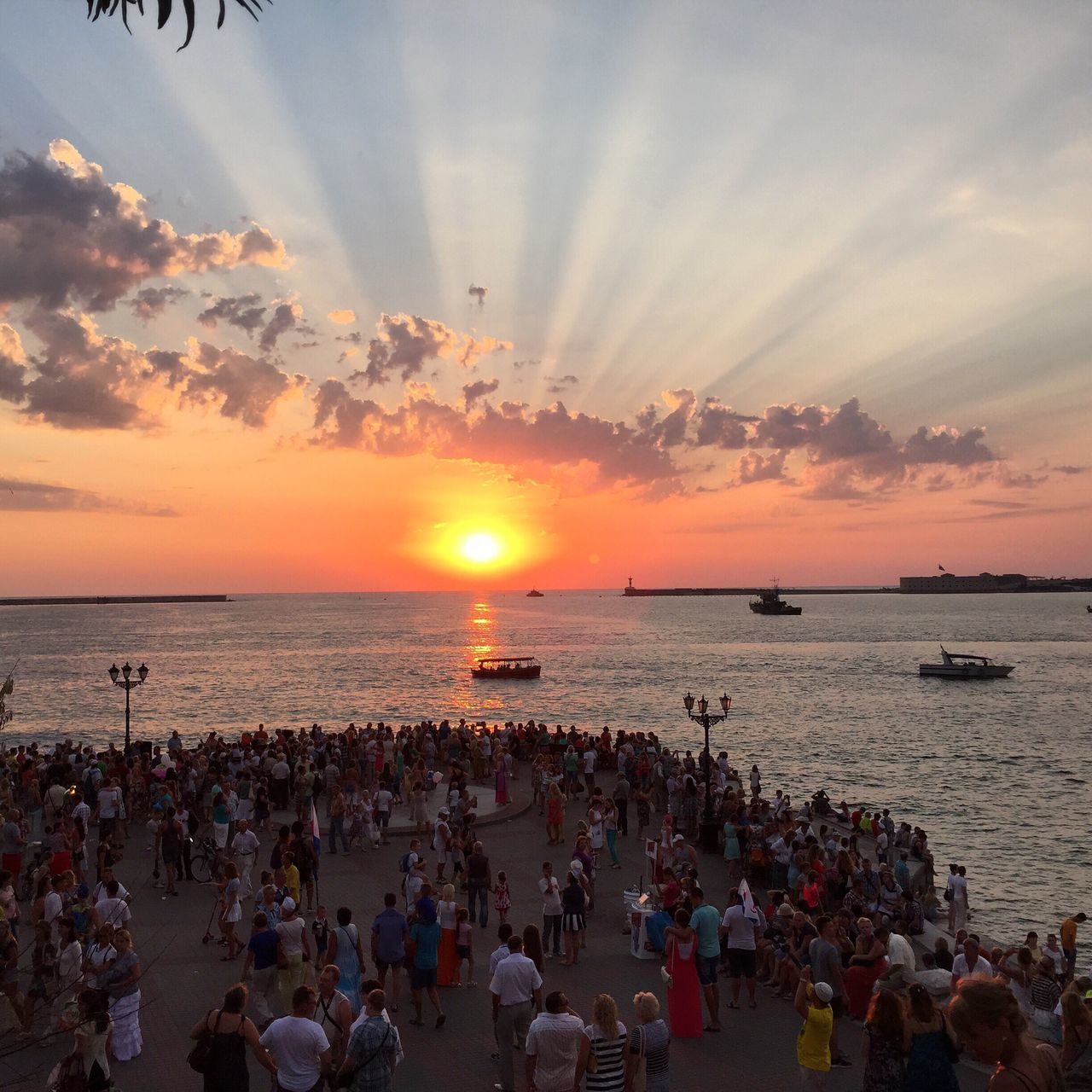 sea, sunset, beach, horizon over water, water, large group of people, sun, beauty in nature, nature, orange color, sky, scenics, leisure activity, real people, lifestyles, outdoors, sand, cloud - sky, women, vacations, crowd, people