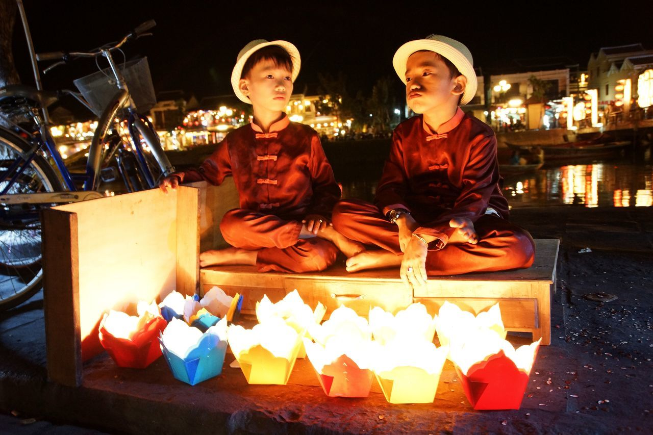 Boys being bored by selling candle-ships to tourists in Vietnam Asian Boys Bored Boys Bored Face Candle Boats Candle Lighting  Colourful Scene Cultures Enlightened Flame Front View Hats In The Shining Light On The Riverside Perspective Real People Selling Candles Sitting Traditional Clothing Learn & Shoot: After Dark Telling Stories Differently Cities At Night Feel The Journey People And Places