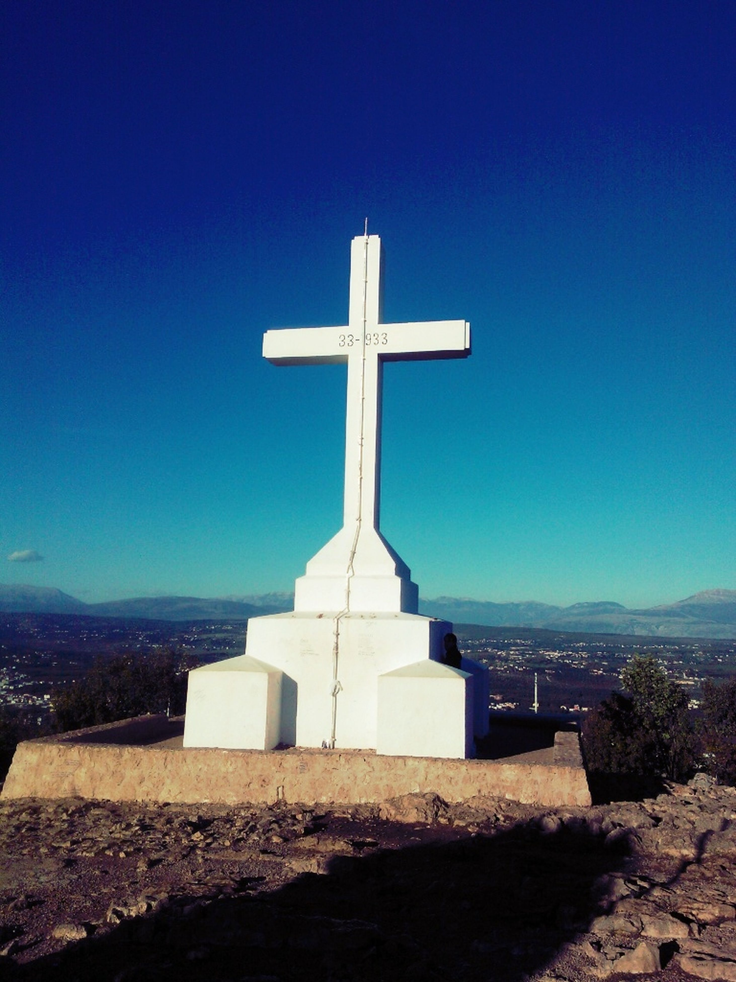 religion, cross, spirituality, clear sky, blue, place of worship, built structure, copy space, church, architecture, building exterior, tower, low angle view, no people, outdoors, sky, day, guidance