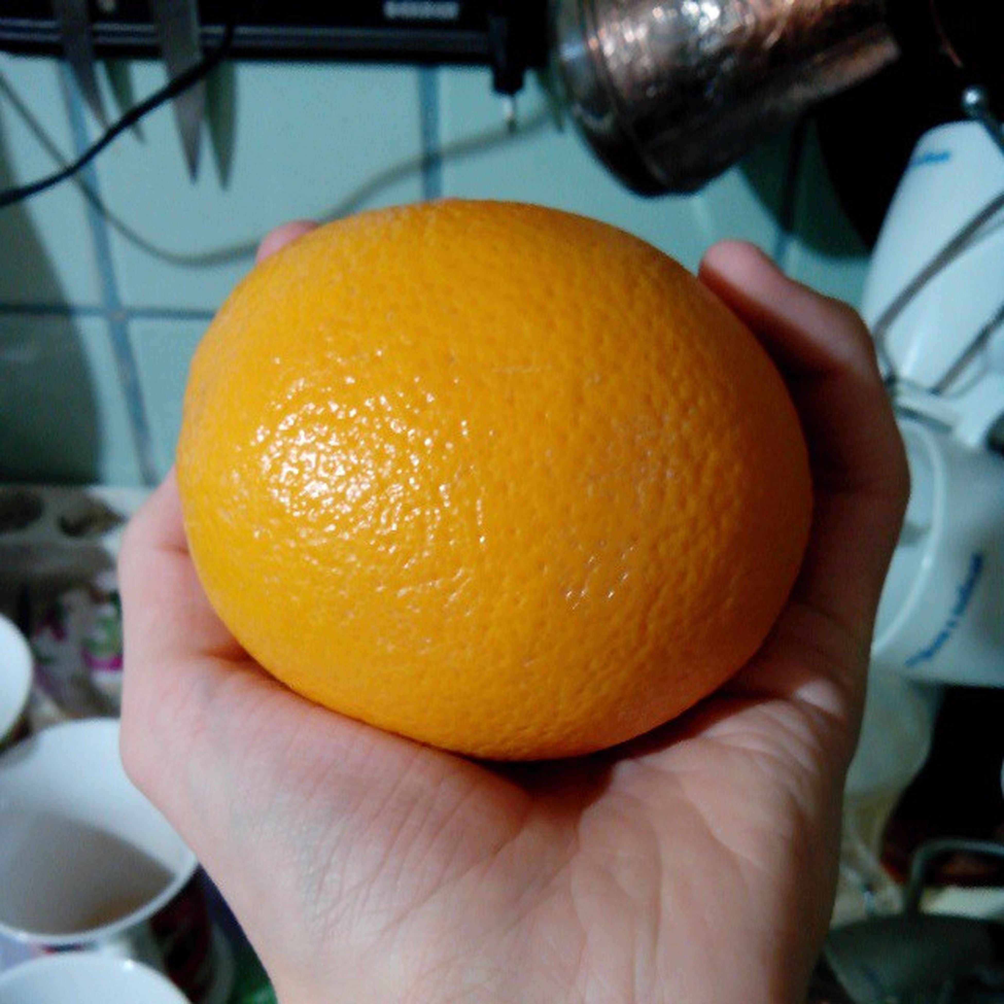 person, food and drink, food, holding, part of, freshness, cropped, unrecognizable person, human finger, personal perspective, close-up, healthy eating, fruit, focus on foreground, lifestyles, orange - fruit, indoors