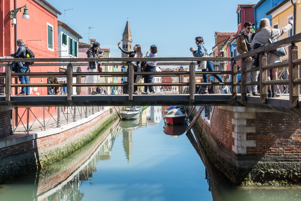 A normal day in Burano Architecture Bridge - Man Made Structure Building Exterior Built Structure Clear Sky Colorful Day Footbridge Lifestyles Men Nature Nautical Vessel Outdoors People Railing Real People Reflection Sky Tourism Tourist Tree Water Waterfront The Street Photographer - 2017 EyeEm Awards