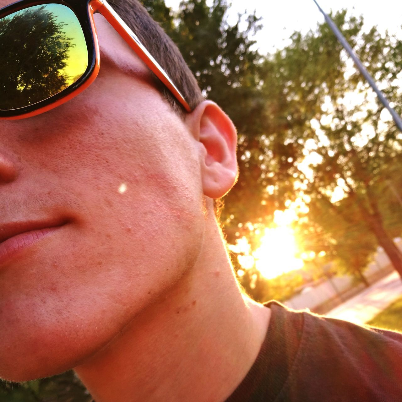 sunglasses, real people, tree, one person, focus on foreground, close-up, day, outdoors, lifestyles, headshot, young adult, people
