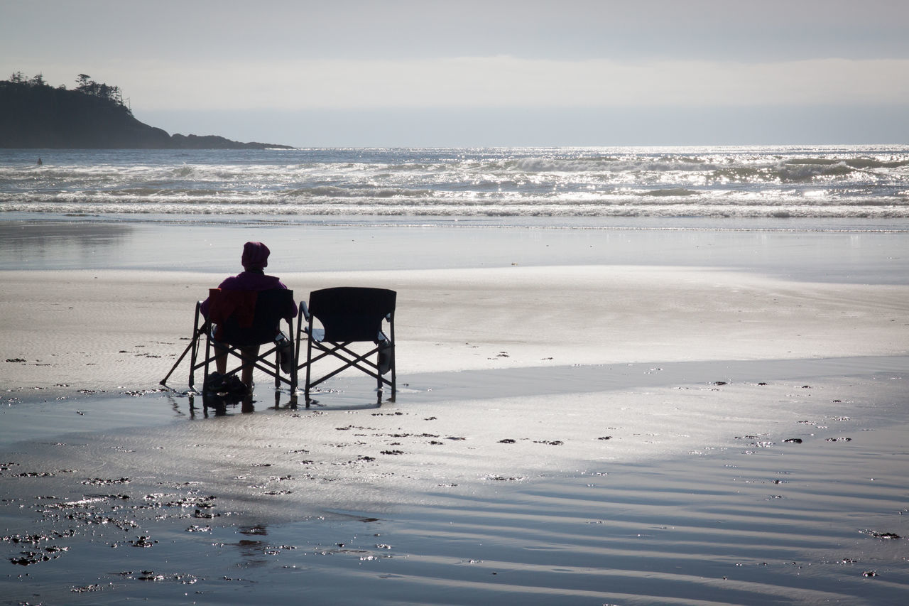 Woman sitting in one of two beach chairs on the beach at low tide Beach Beauty In Nature Horizon Over Water Idyllic Nature Non-urban Scene Person Rear View Relaxation Remote Sand Scenics Sea Shore Sitting Sky Tourism Tranquil Scene Tranquility Travel Destination Travel Destinations Vacations Vancouver Island Canada Water Wave