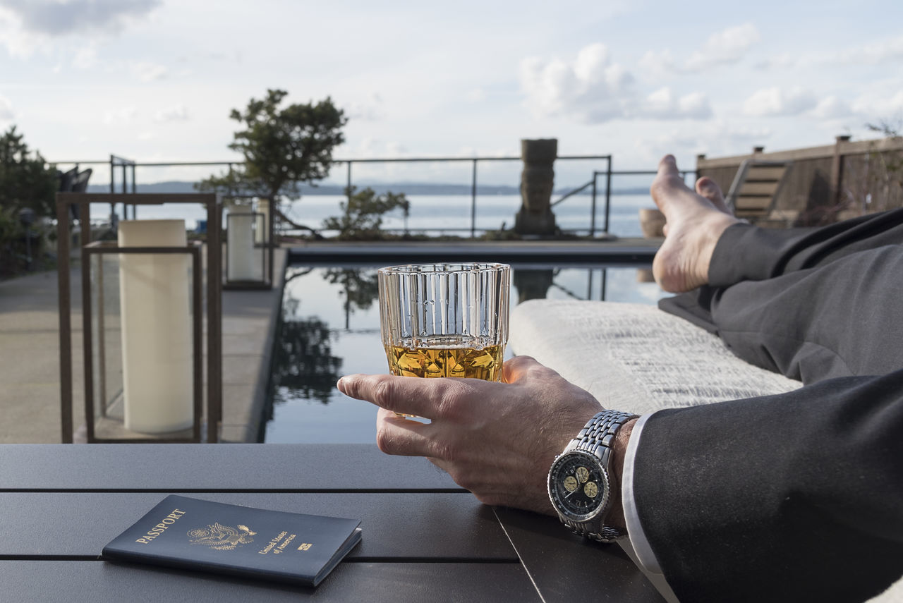 Businessman enjoying drink by the pool with passport Adult Adults Only Business Businessman City Communication Connection Day Drink Holding Human Body Part Human Hand Men One Man Only One Person Only Men Outdoors Passport People Portable Information Device Sky Suit Table Technology Wireless Technology