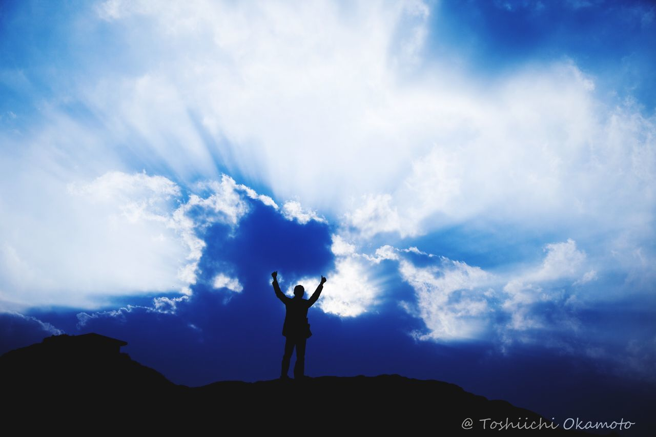 cloud - sky, sky, silhouette, real people, beauty in nature, outdoors, leisure activity, nature, one person, men, standing, scenics, day, lifestyles, low angle view, blue, energetic