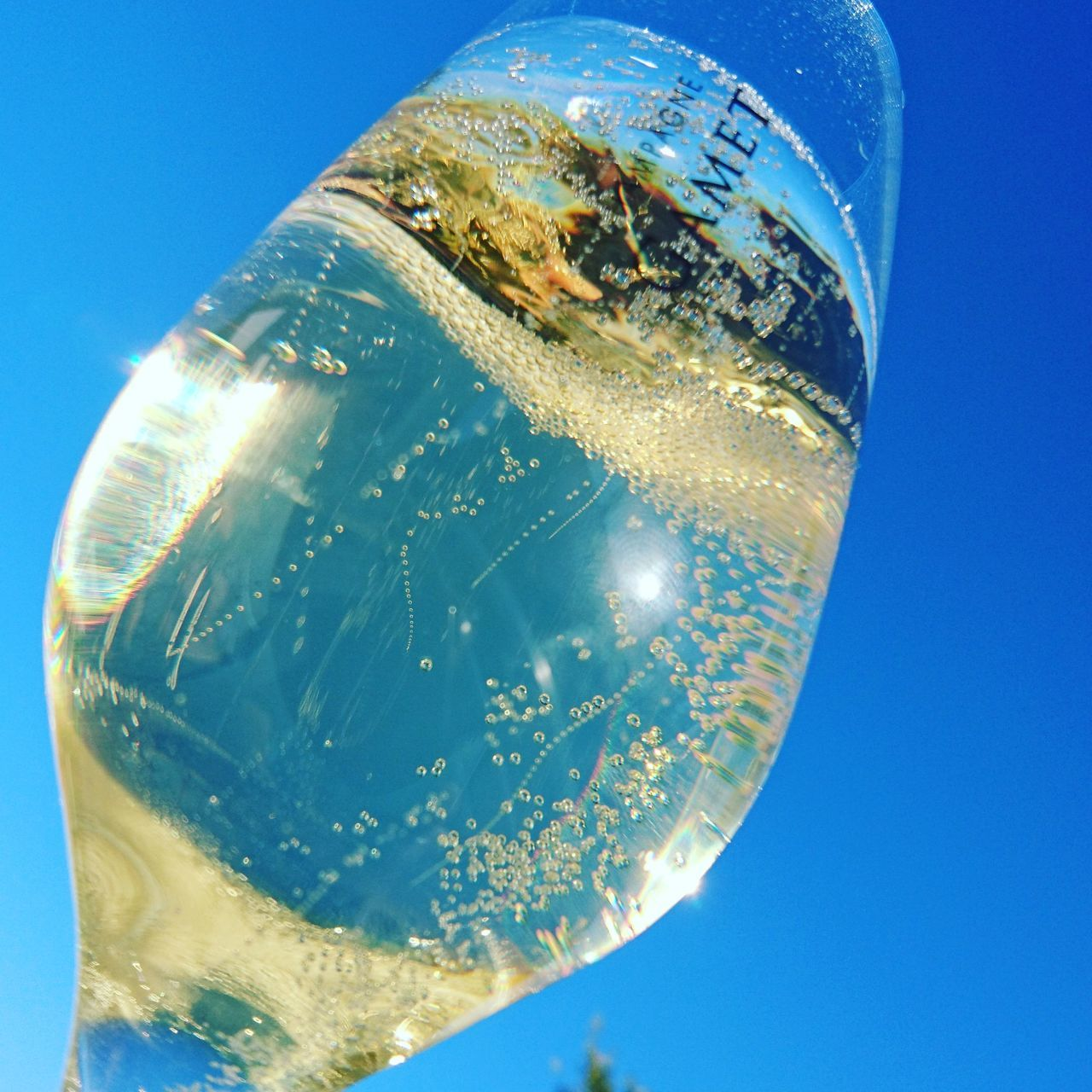 A glas of bubbles framed by the beatiful clear blue sky Blue Bubble Cava Clear Sky Alcohol Food And Drink Refreshment Champagne