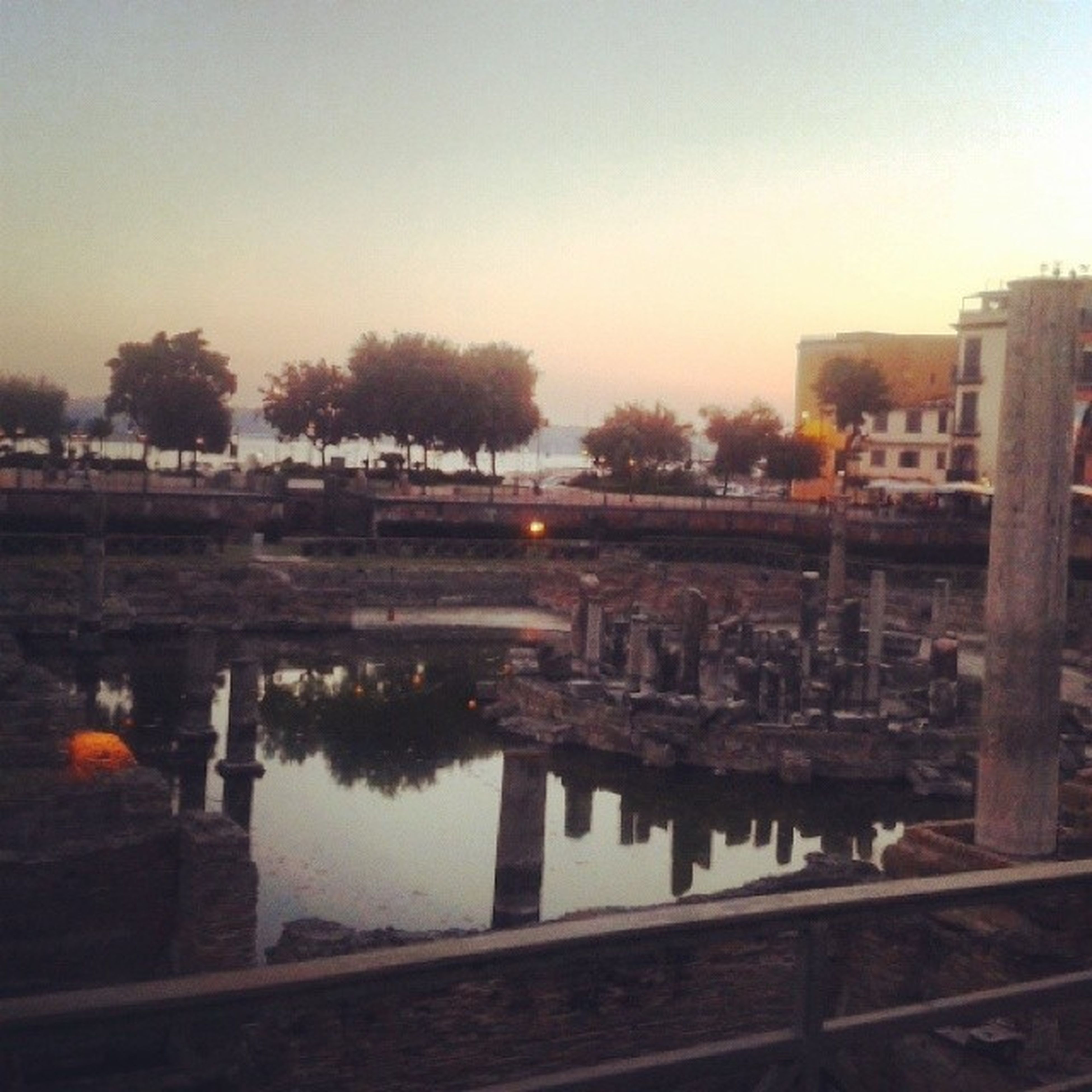 water, reflection, built structure, architecture, building exterior, clear sky, lake, river, standing water, sunset, sky, canal, tree, nature, dusk, outdoors, waterfront, season, city, copy space
