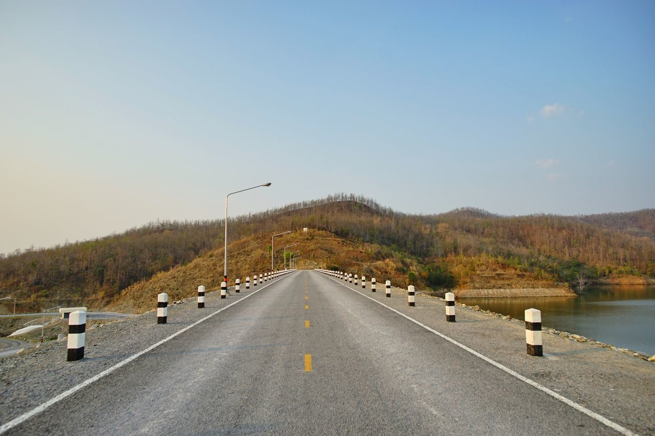Empty Road Leading Towards Mountain Against Clear Sky