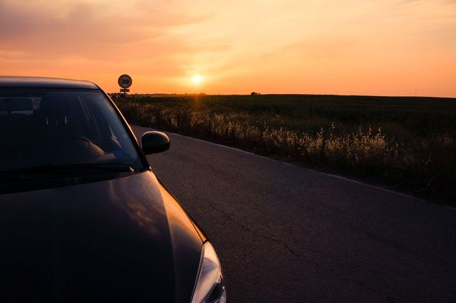Atmosphere Car Cropped Escapism Field Getting Away From It All Journey Land Vehicle Landscape Mode Of Transport On The Move Part Of Road Sky Sunset The Way Forward Transportation Travel