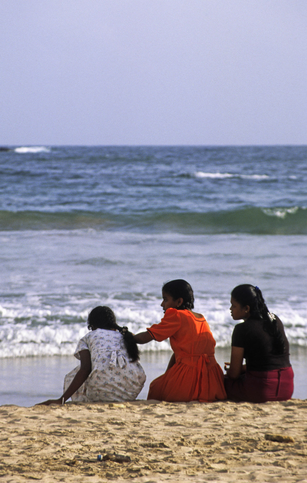 Three young girls sit on a Sri Lankan beach Beach Day Friends Horizon Over Water Idyllic Leisure Activity Lifestyles Ocean Outdoors Relaxation Remote Scenics Sea Seascape Shore Sitting Sky Three Girls Togetherness Tourism Tranquil Scene Vacations Water Wave