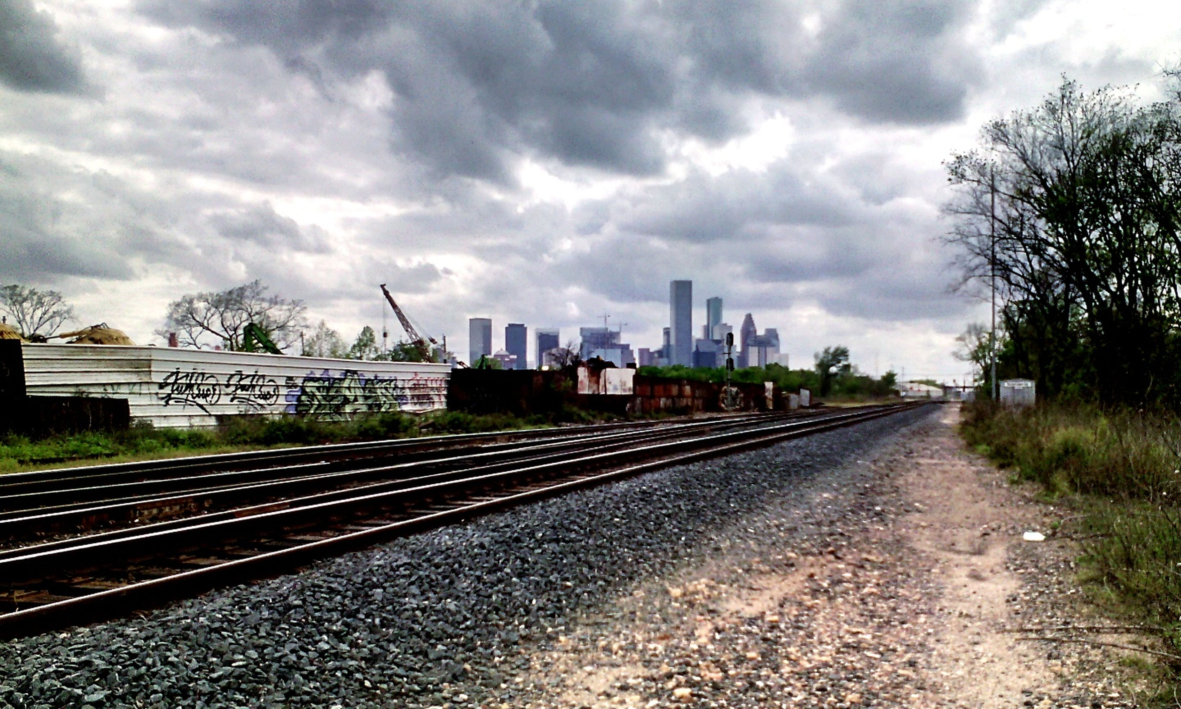 sky, cloud - sky, building exterior, architecture, railroad track, built structure, cloudy, rail transportation, cloud, the way forward, transportation, diminishing perspective, tree, overcast, city, vanishing point, day, road, weather, outdoors