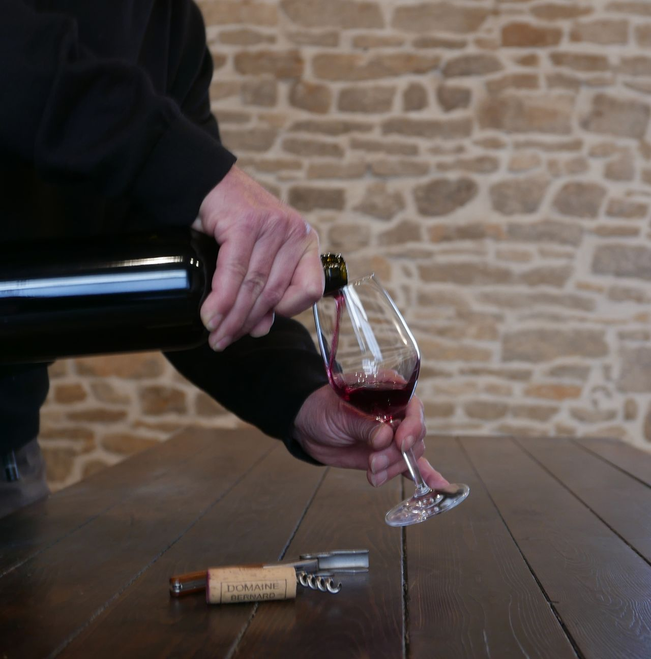 Man pouring red wine from a bottle into a glass. Open bottle of wine Cork Glass Corkscrew On a table In a cellar wine tasting France Wine Tasting