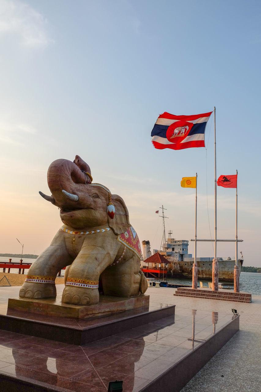 statue, sculpture, art and craft, flag, animal representation, patriotism, sky, no people, outdoors, day, travel destinations