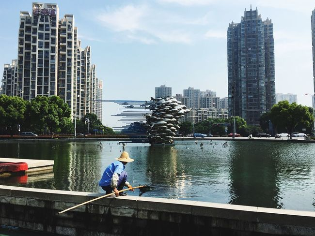 Flying Fishes City Building Exterior Tree Water Architecture Built Structure Skyscraper Men Tower River Sky Tall - High Office Building City Life Vacations Urban Skyline Day Outdoors Building Story Canal Fish Man Quiet Moments Fountain