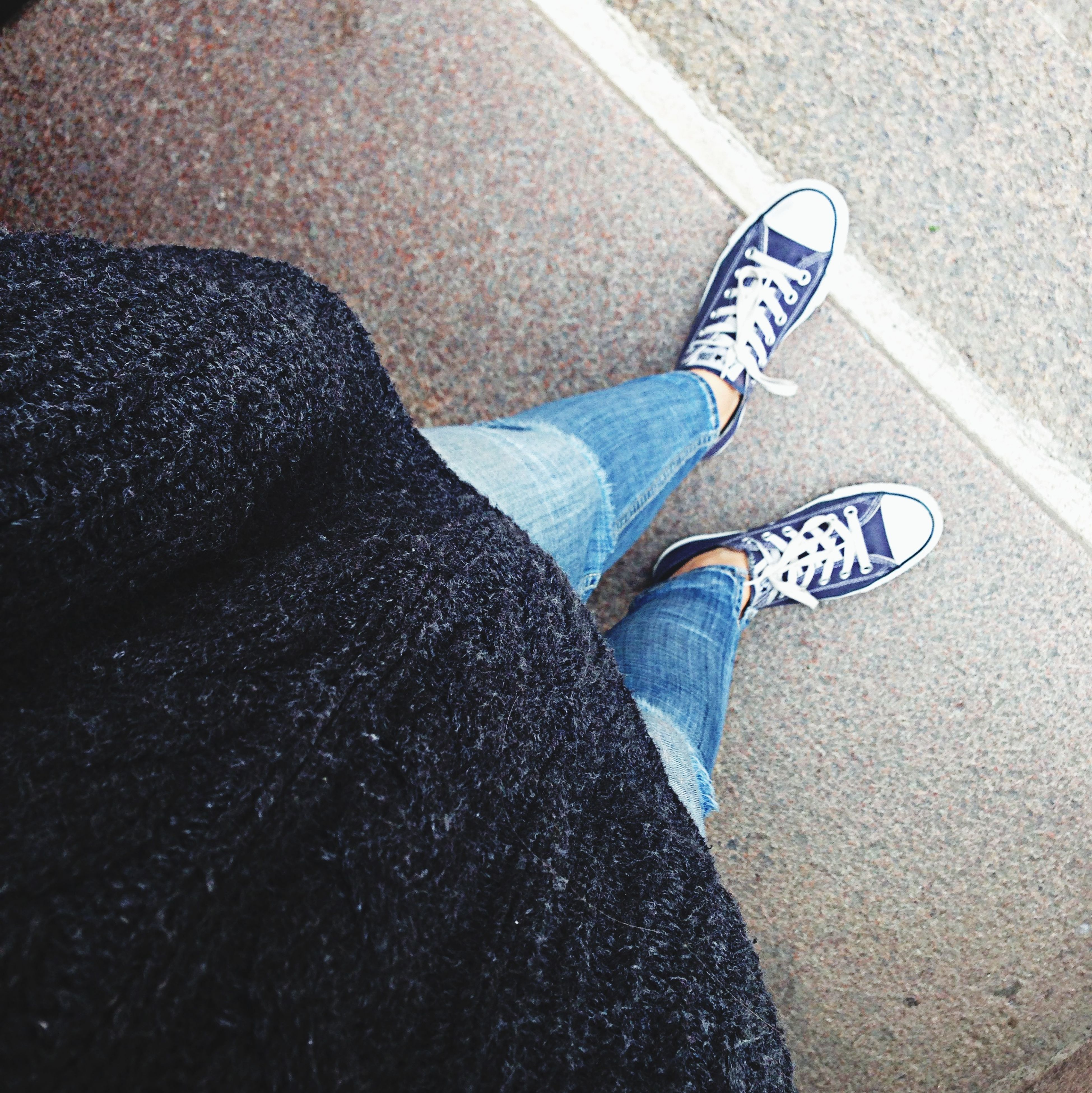 low section, person, shoe, lifestyles, high angle view, jeans, personal perspective, leisure activity, standing, casual clothing, footwear, blue, human foot, men, relaxation, directly above, day