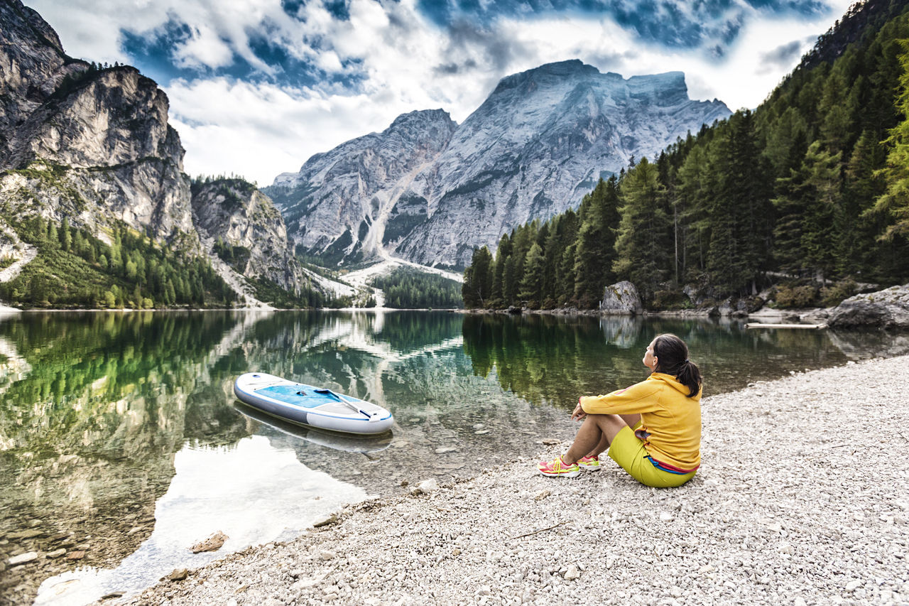 Woman sitting at the Pragser Wildsee before standup paddleboarding Alone Alps Dolomites Enjoyment Lake Leisure Activity Lifestyles Mountain Nature Outdoors Paddleboarding Prags Pragser Wildsee Quiet Moments Reflection Relaxing Sitting Standup Paddleboarding Standuppaddle Sup Südtirol Tranquil Scene Tranquility Vacations Water