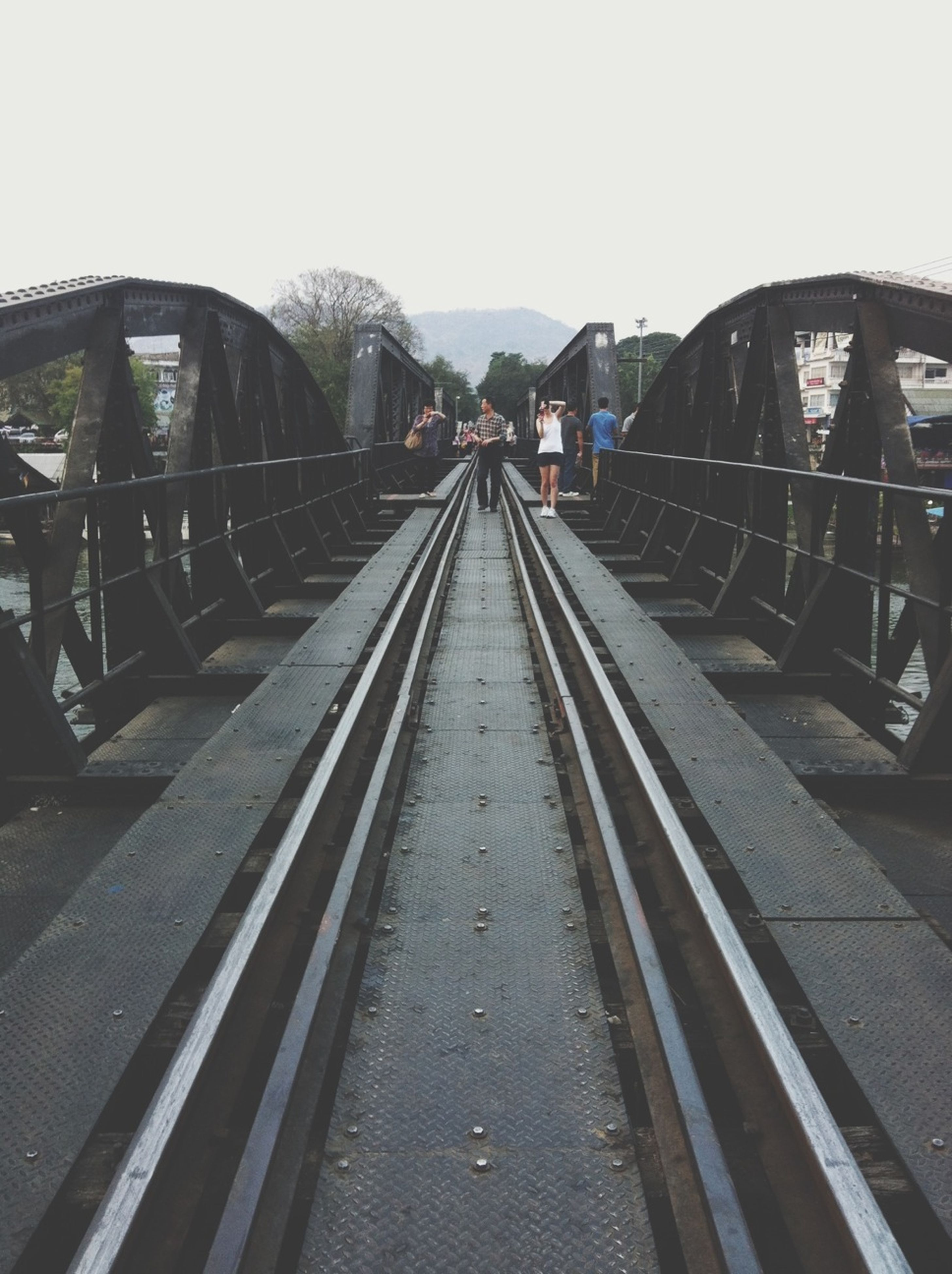 transportation, clear sky, railroad track, rail transportation, diminishing perspective, the way forward, connection, built structure, bridge - man made structure, vanishing point, railing, sky, copy space, mode of transport, architecture, day, metal, public transportation, outdoors, travel