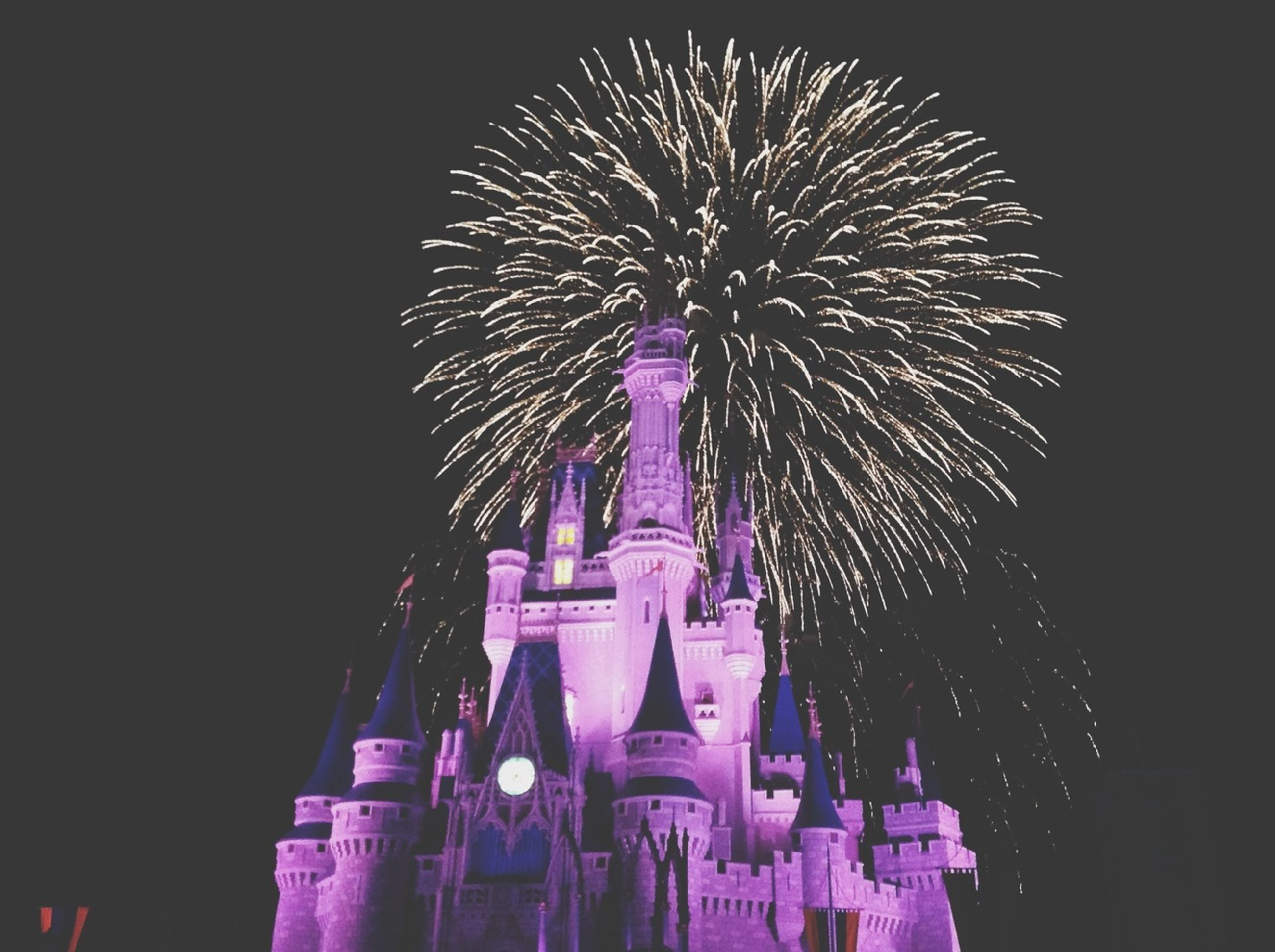 night, illuminated, low angle view, celebration, arts culture and entertainment, firework display, firework - man made object, long exposure, exploding, motion, event, building exterior, architecture, built structure, blurred motion, sky, glowing, entertainment, sparks, clear sky