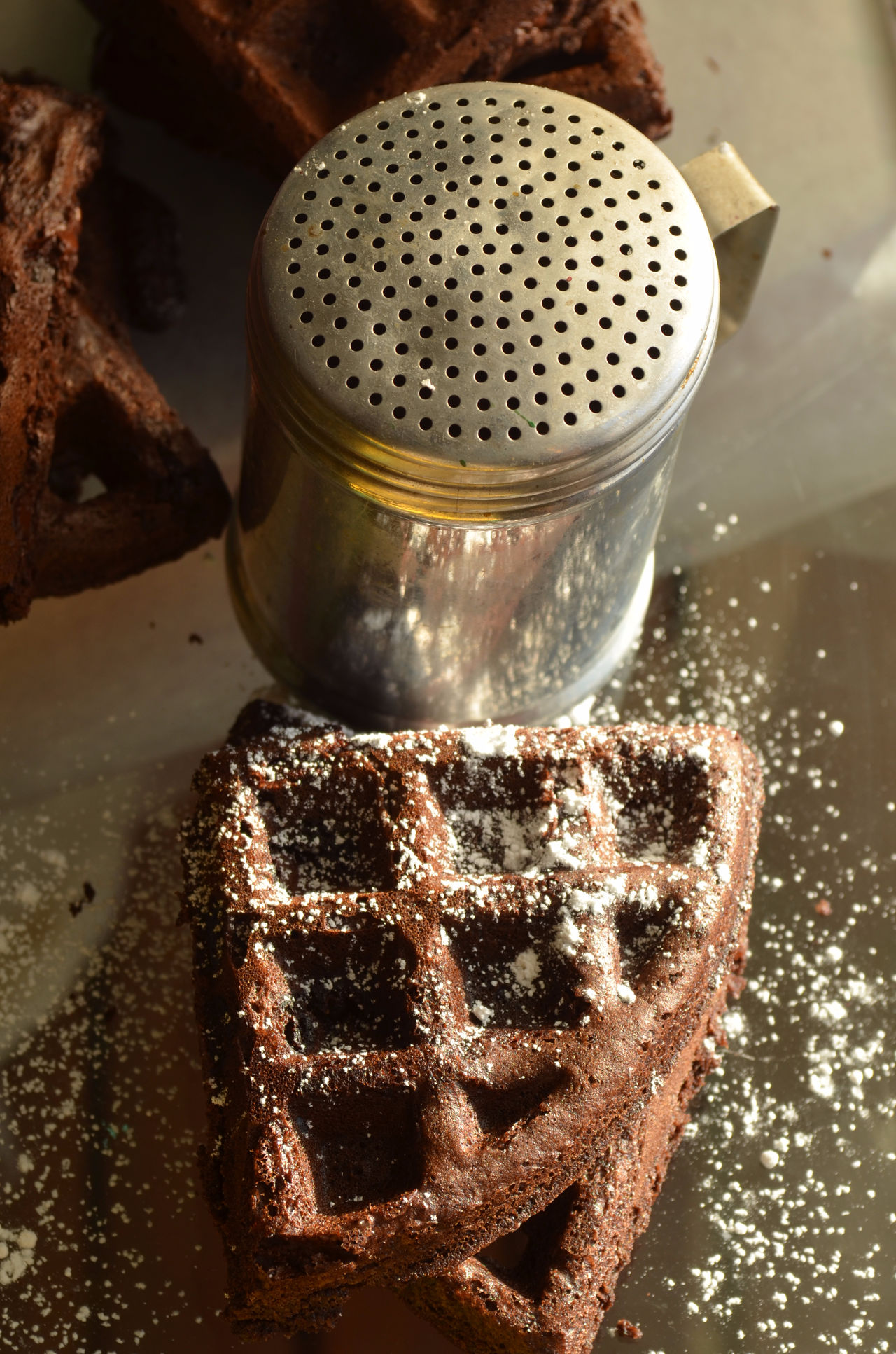 chocolate brownie waffles sprinkled with powdered sugar and metal sugar shaker Baked Chocolate Food Fresh Indoors  No People Powdered Sugar Ready To Eat Shaker Waffle Waffles