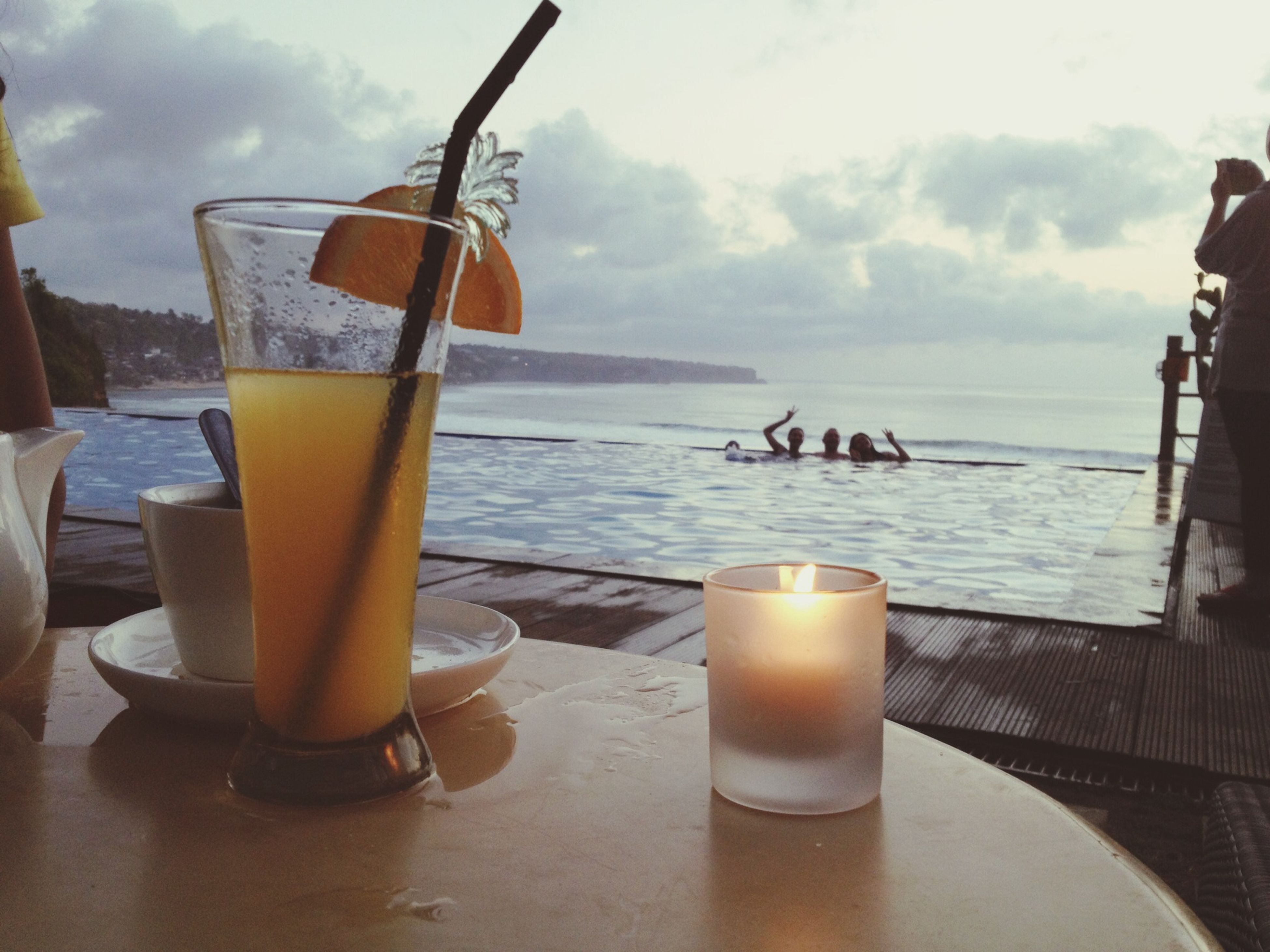drink, food and drink, refreshment, table, sea, sky, drinking glass, freshness, water, cloud - sky, horizon over water, beach, drinking straw, alcohol, beverage, sunset, cloud, outdoors, close-up, frothy drink