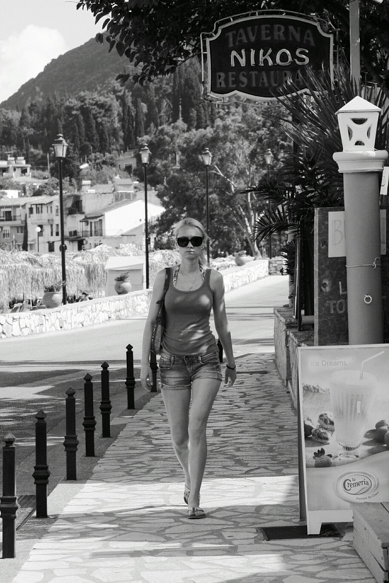 Young Women Full Length Front View Walking Street On Holiday Restaurant Corfu Mountains In Background Street Photography