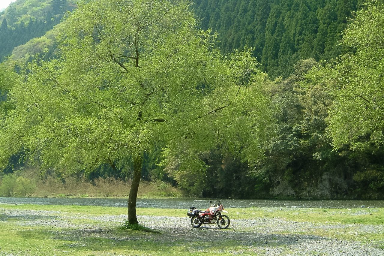Motorcycle Parked On Field Against River And Mountains