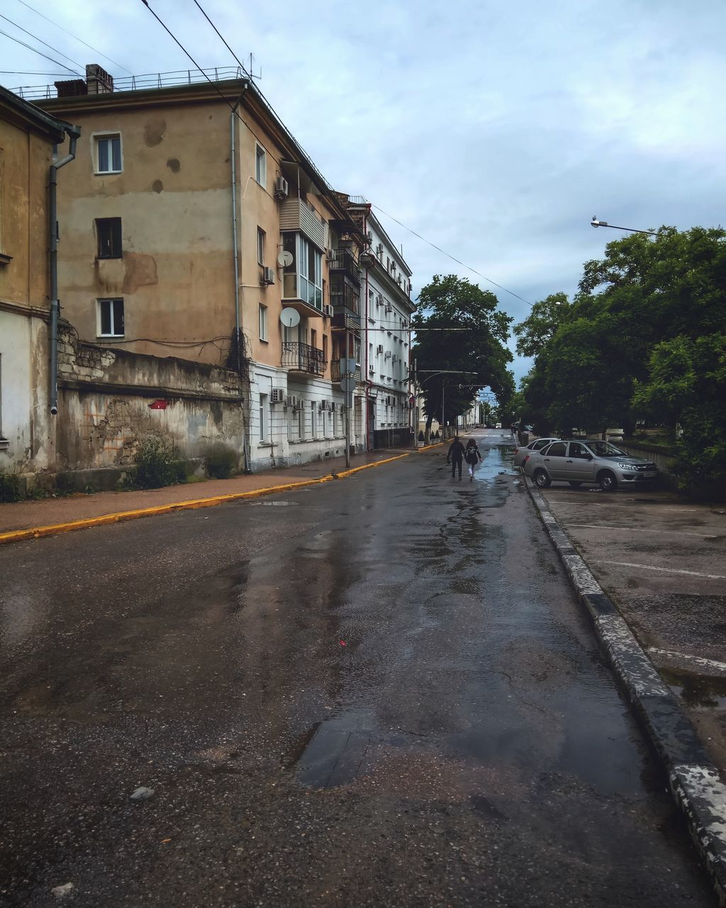 built structure, architecture, building exterior, sky, road, street, cloud - sky, house, wet, water, outdoors, residential building, day, tree, the way forward, puddle, no people, city
