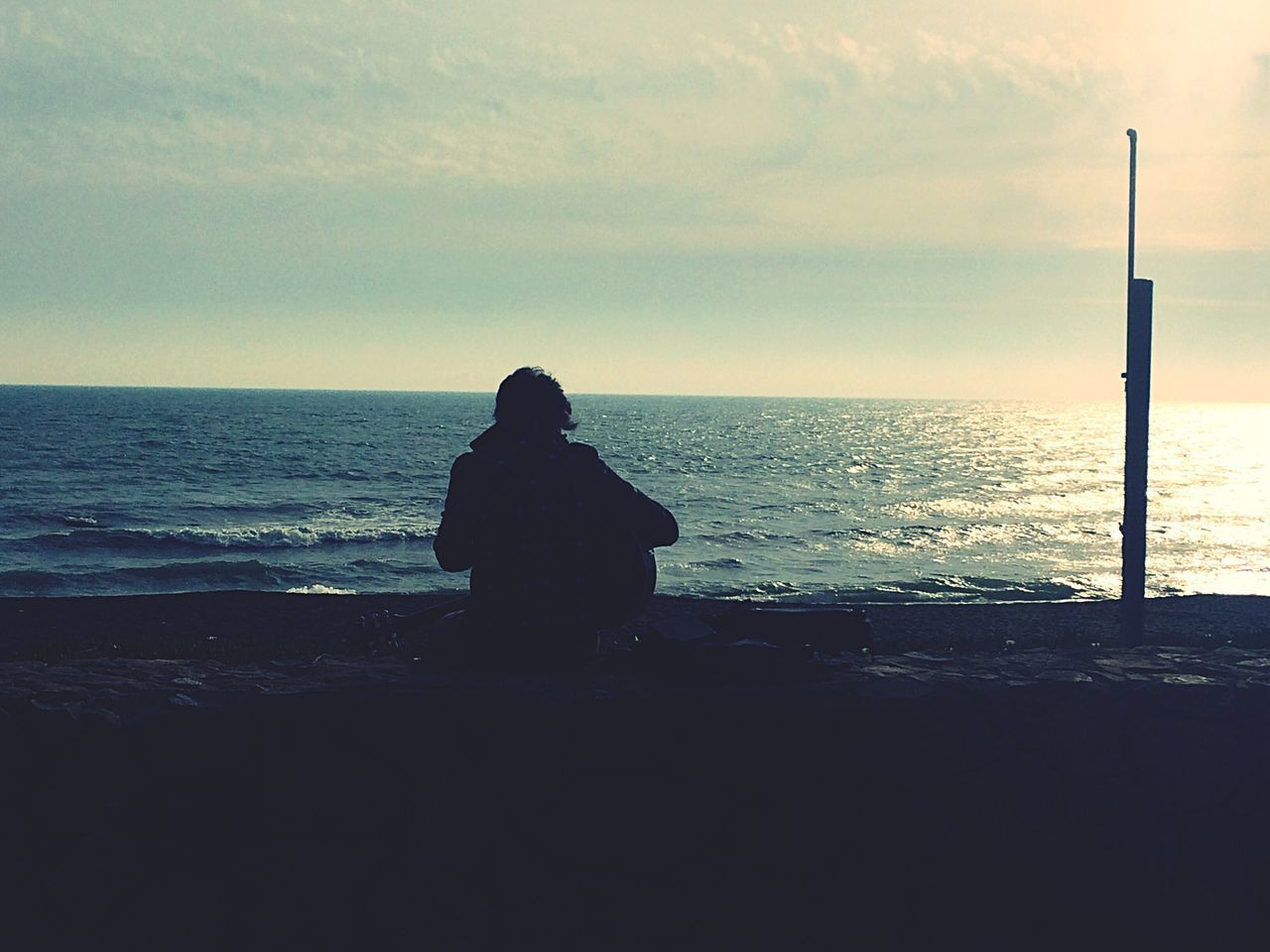 sea, horizon over water, water, nature, silhouette, beauty in nature, tranquil scene, scenics, beach, one person, sky, standing, tranquility, real people, rear view, leisure activity, outdoors, sunset, vacations, men, full length, day, people