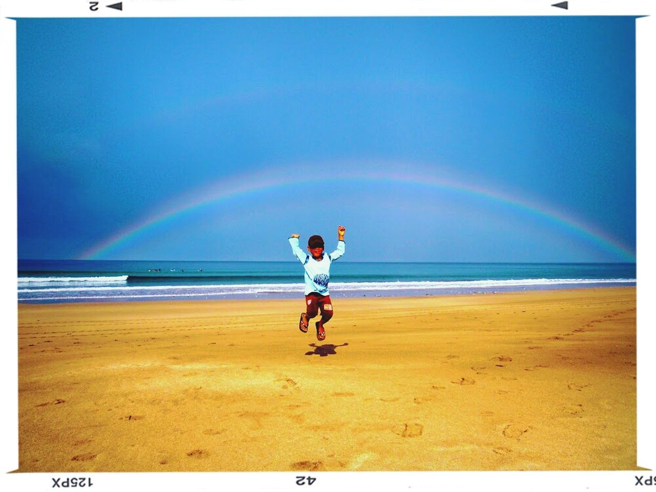 beach, sea, sand, full length, horizon over water, rainbow, water, day, outdoors, nature, scenics, standing, leisure activity, one person, real people, vacations, sky, beauty in nature, young adult, people