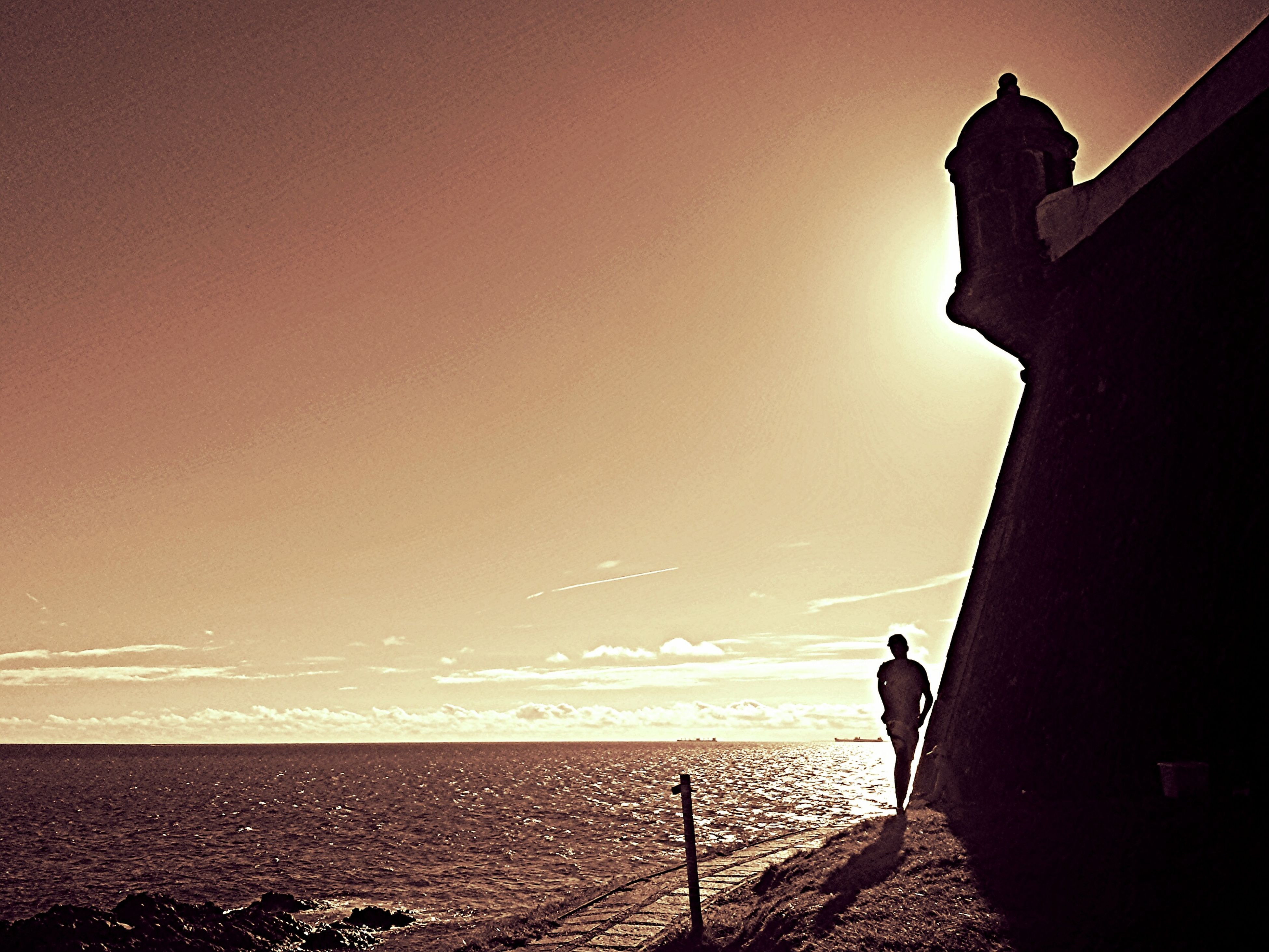 sea, silhouette, horizon over water, water, sky, sunset, built structure, railing, scenics, tranquility, architecture, full length, standing, copy space, nature, tranquil scene, men, beach