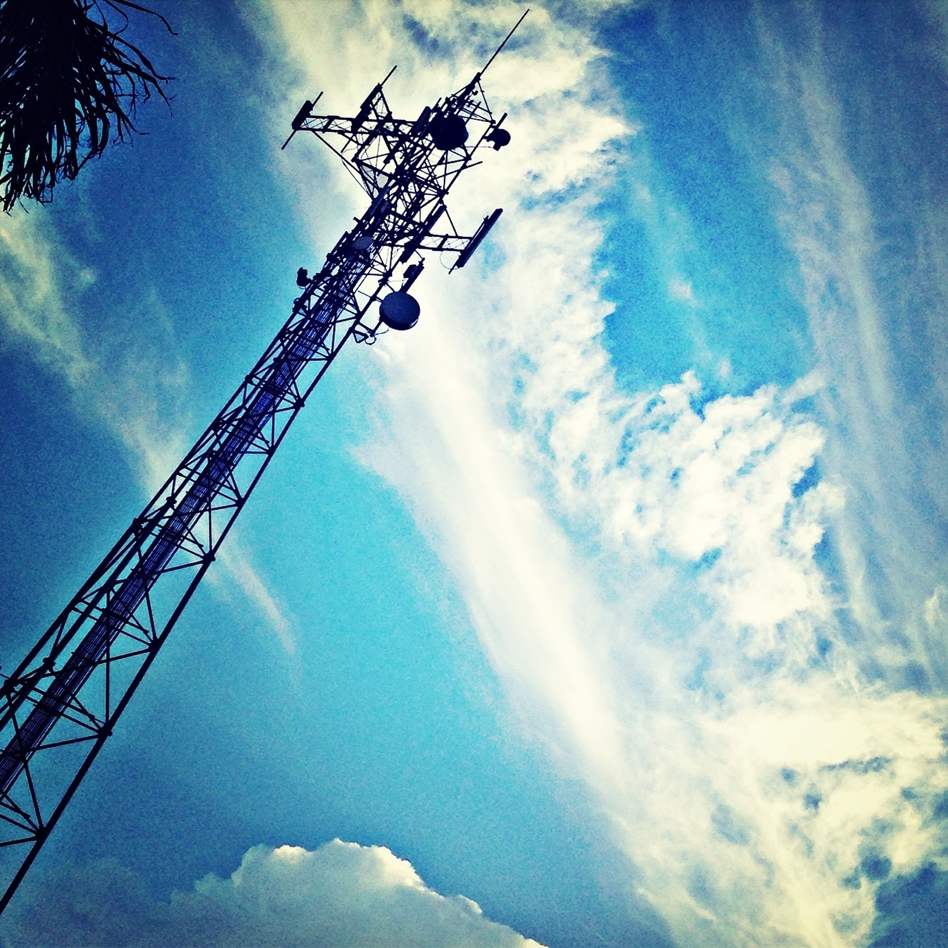 low angle view, sky, cloud - sky, blue, cloudy, cloud, vapor trail, sunbeam, day, nature, technology, sunlight, outdoors, no people, tall - high, electricity, fuel and power generation, beauty in nature, weather, silhouette