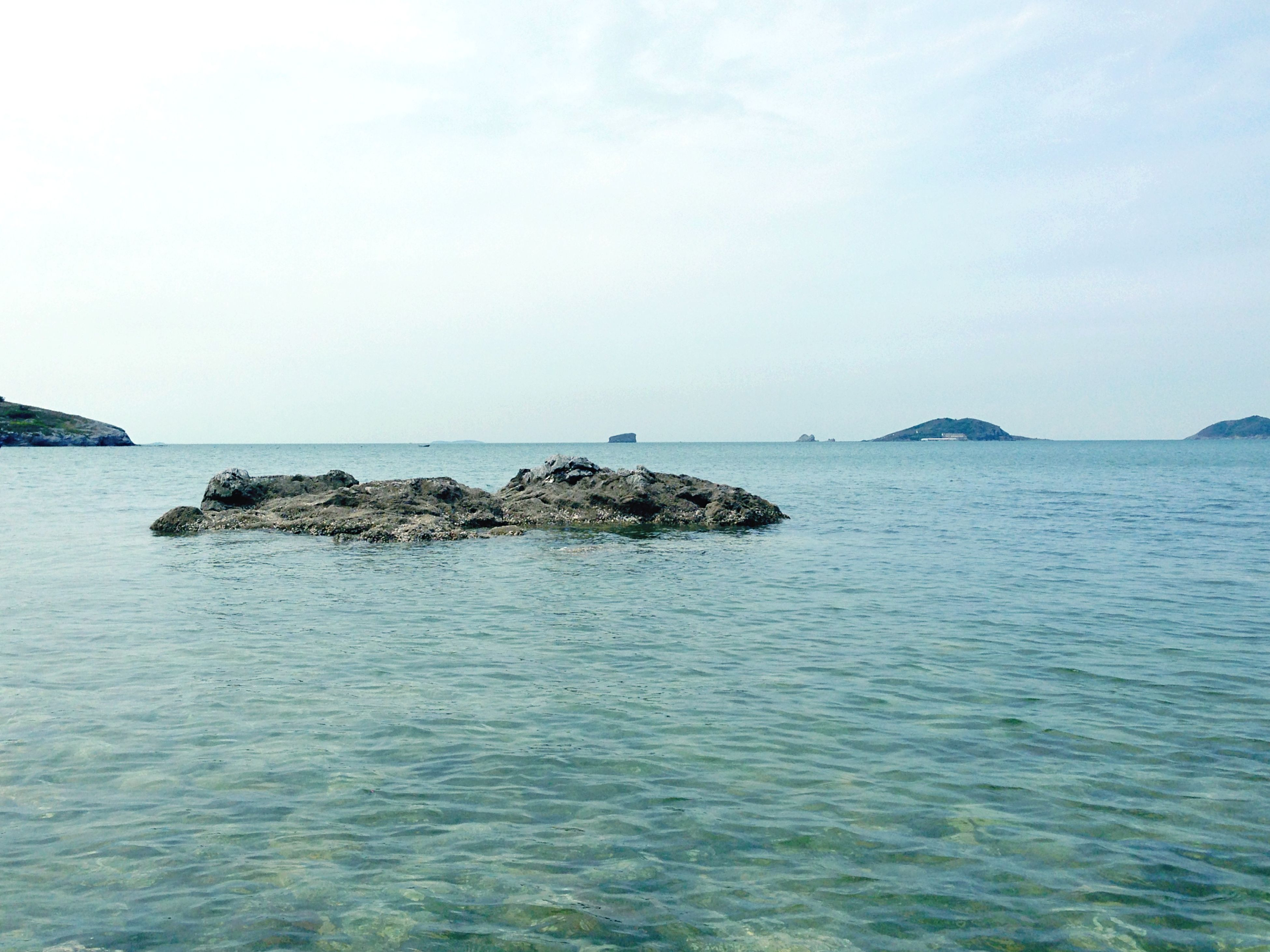 sea, water, horizon over water, tranquil scene, tranquility, scenics, beauty in nature, waterfront, nature, sky, rippled, idyllic, copy space, rock - object, blue, rock formation, clear sky, seascape, day, outdoors